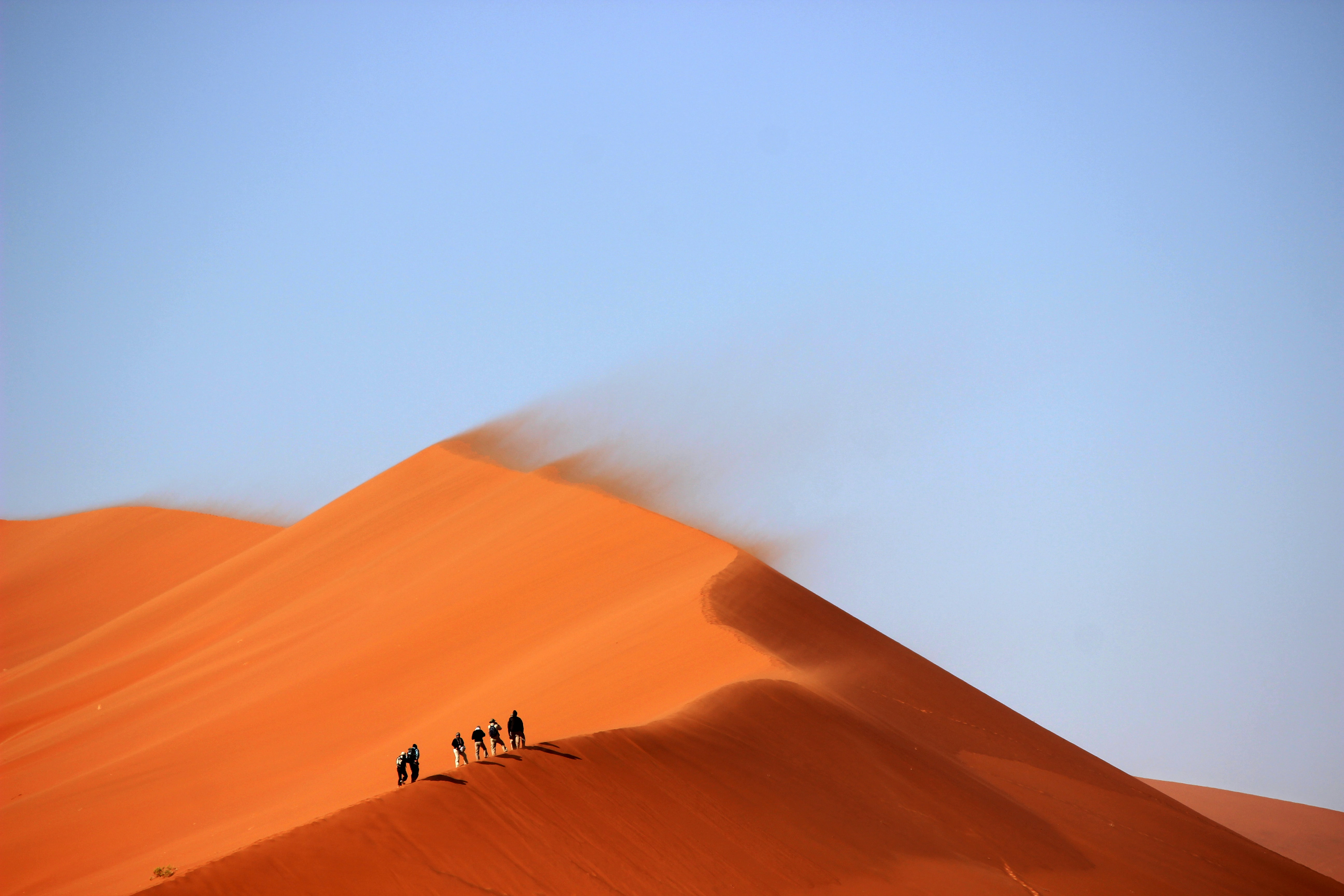 Hikers walk along orange sand ridges on a windy foggy day