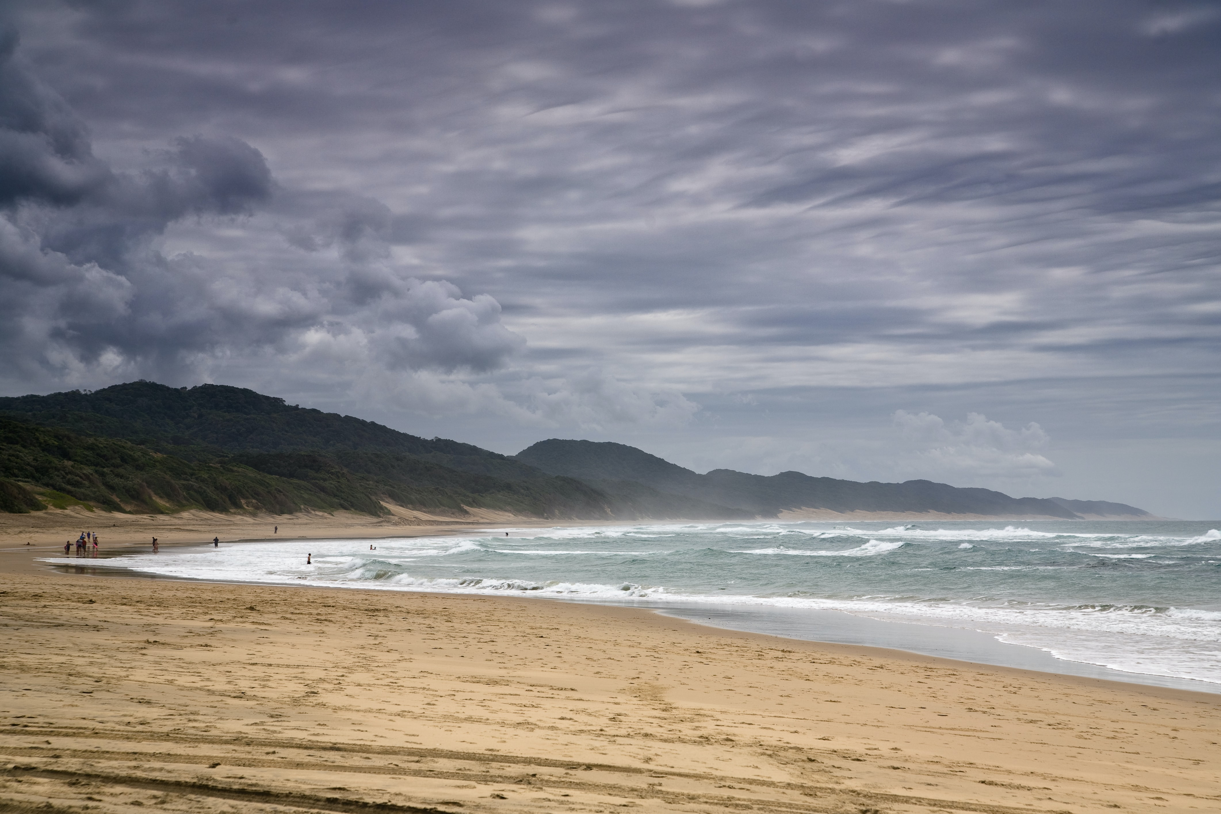 coastline, stormy waters, ocean shore and mountains forge a beautiful beach view.