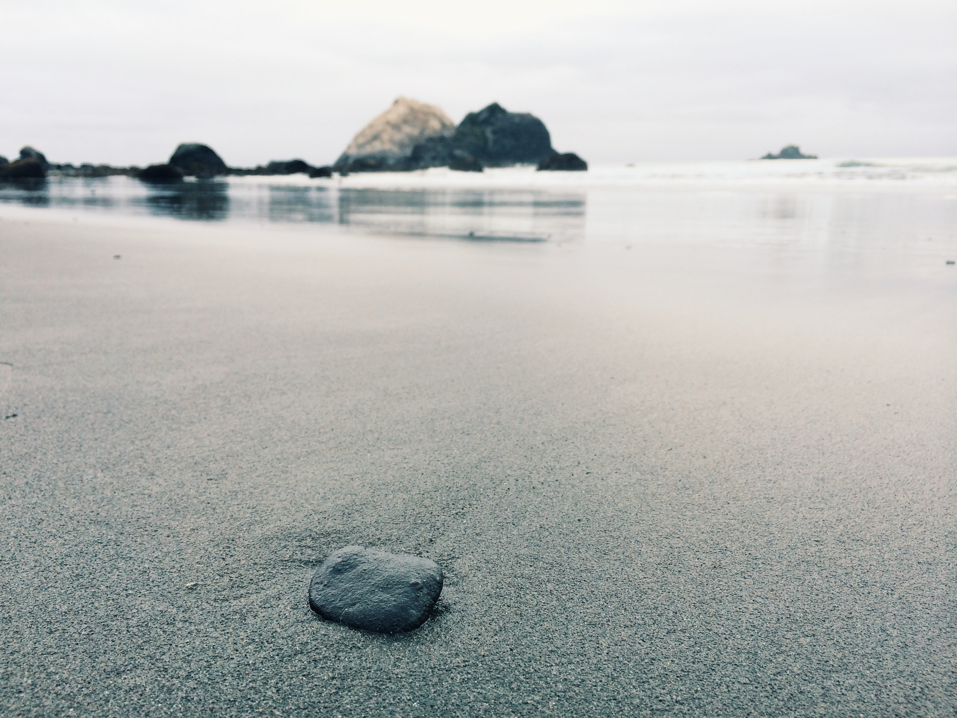 Small rock on the fine wet sand beach coast
