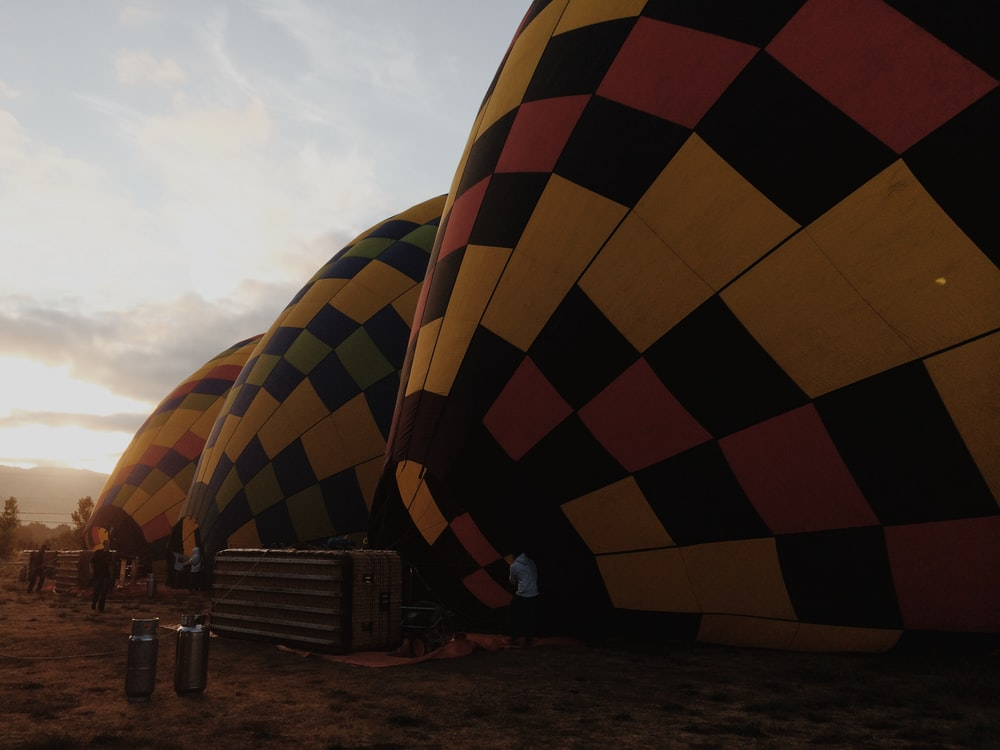 three inflated multicolored hot air balloons on the field