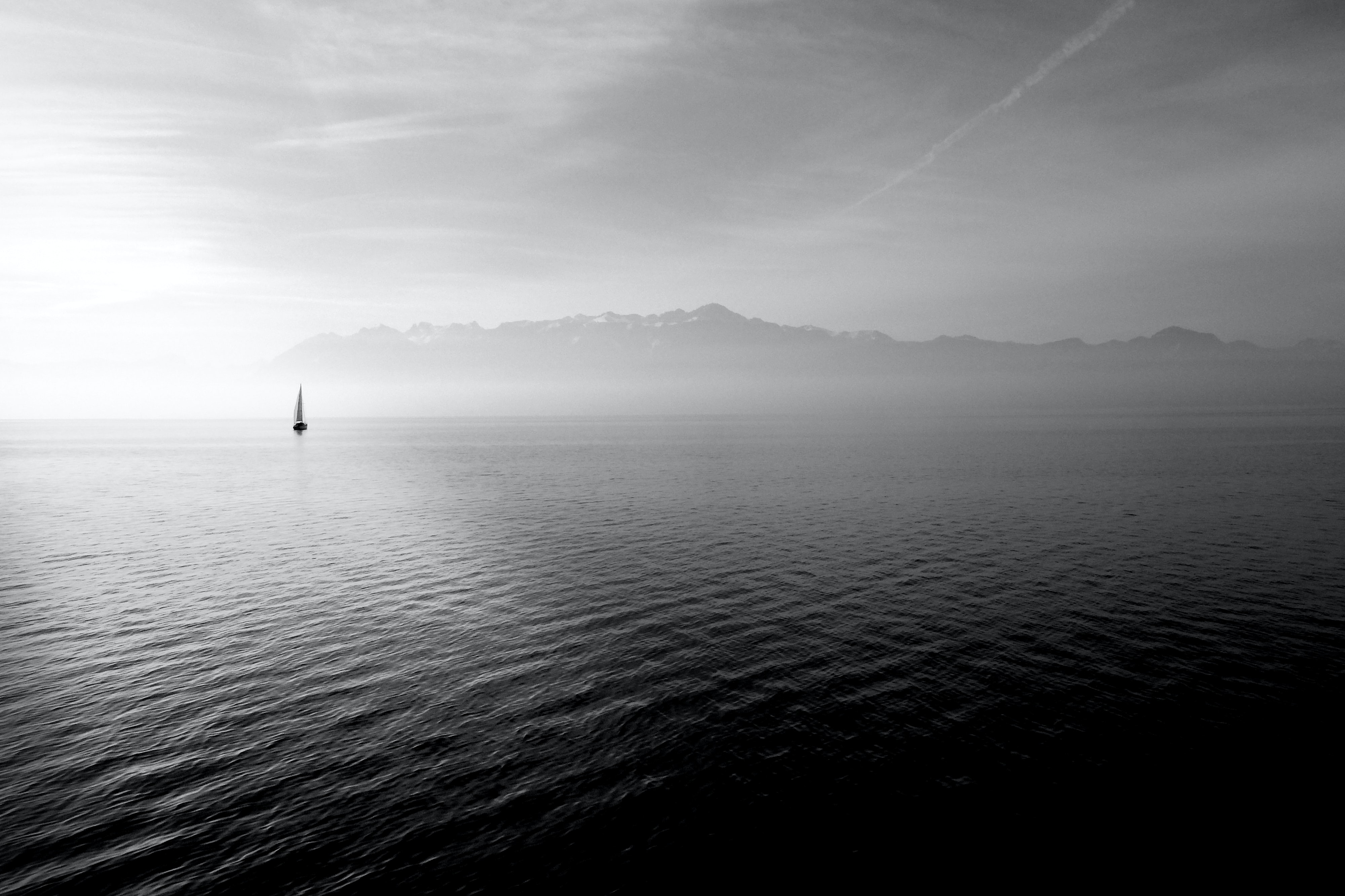 Sailboat sits on the horizon of a calm oceanscape
