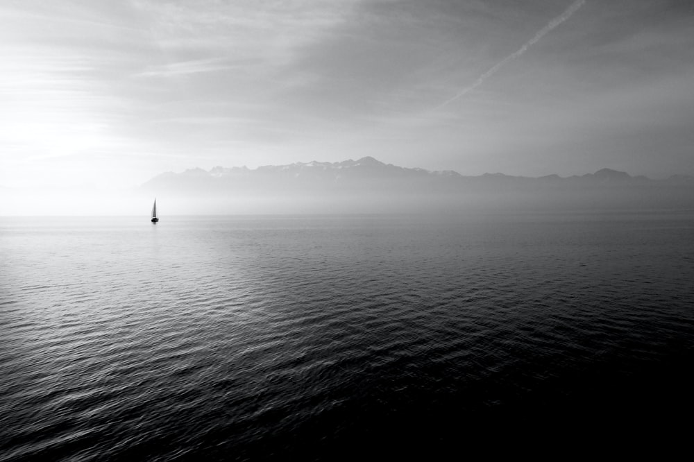 sailboat on calm body of water under white sky at daytime