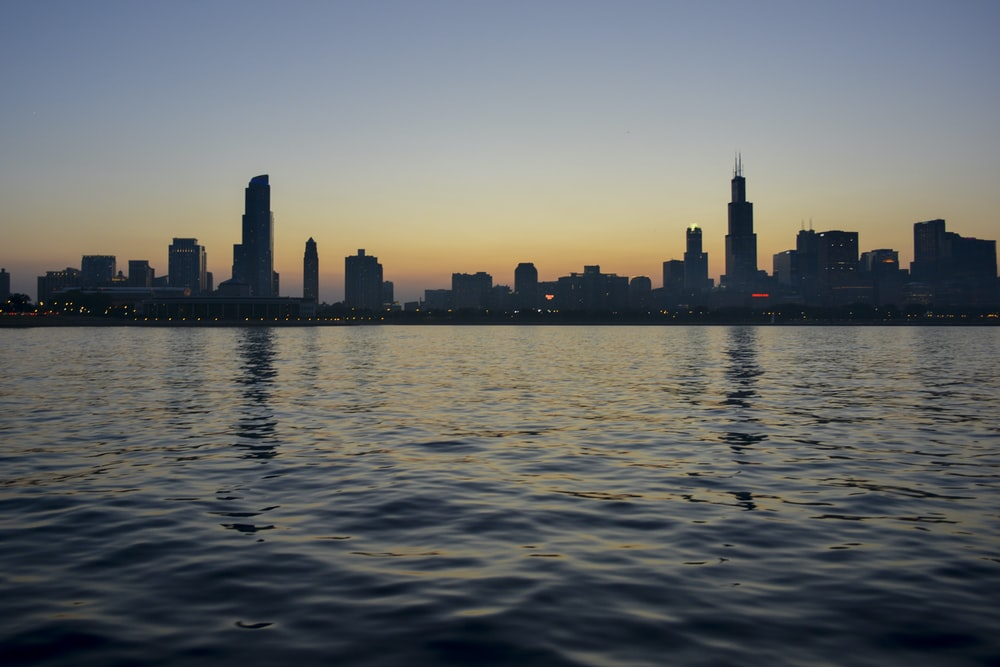 silhouette of city skyline near body of water