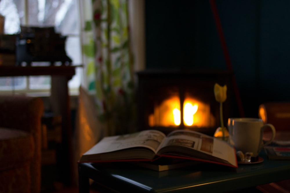 A book and coffee mug sitting on a table in a cozy den lit by firelight