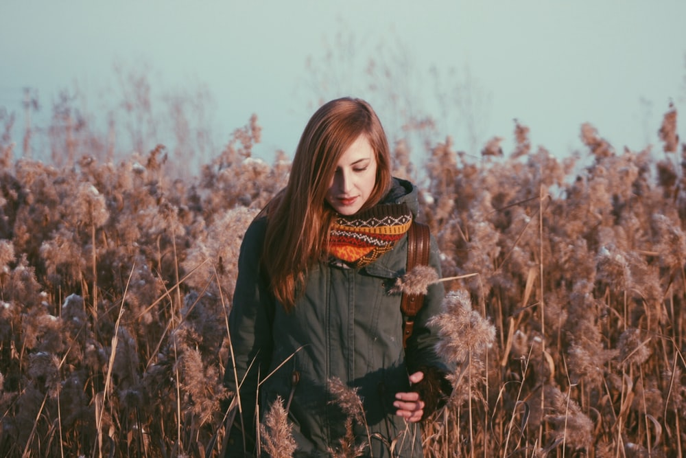 woman standing near grey flowers