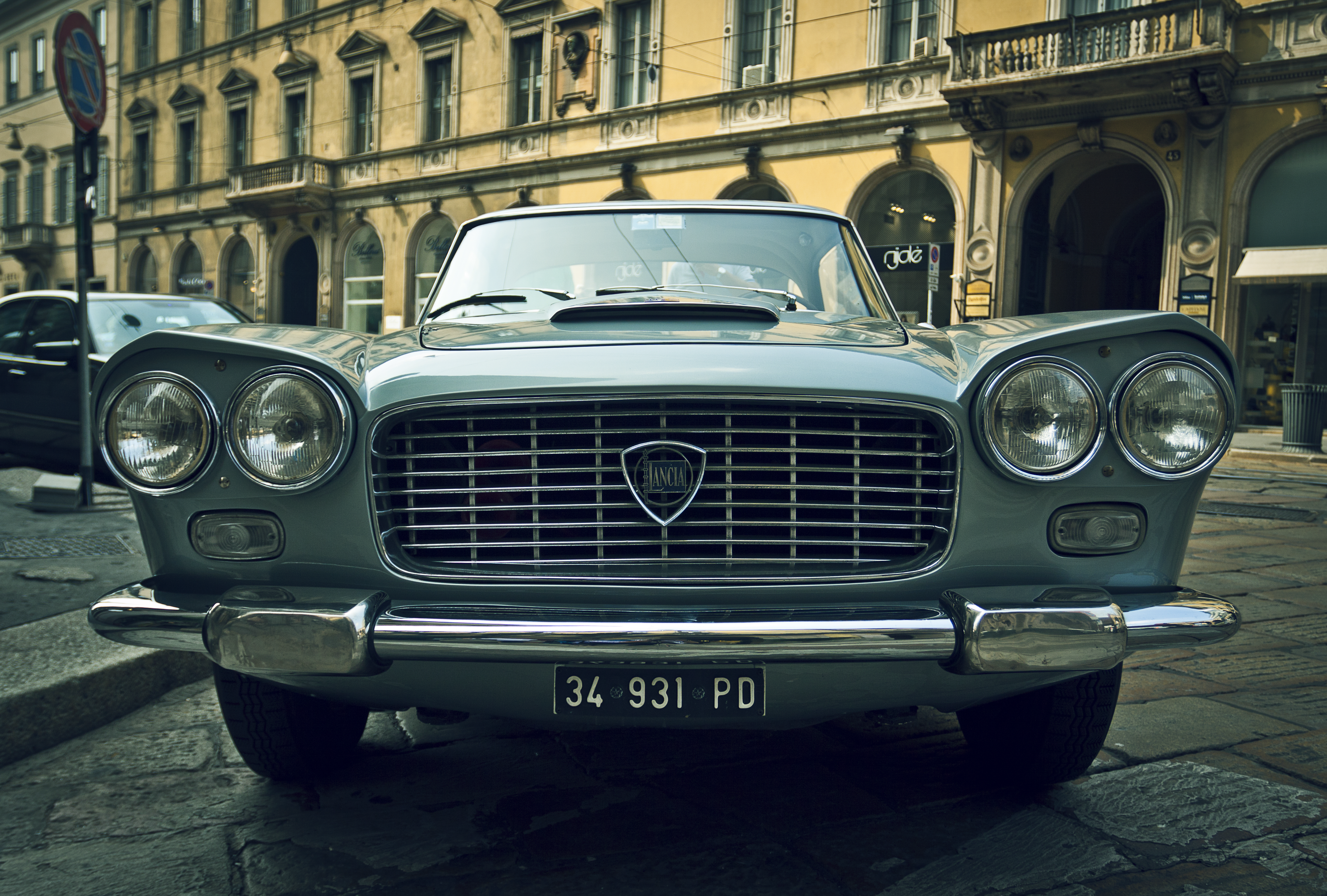 Front view of a vintage car in a European city.