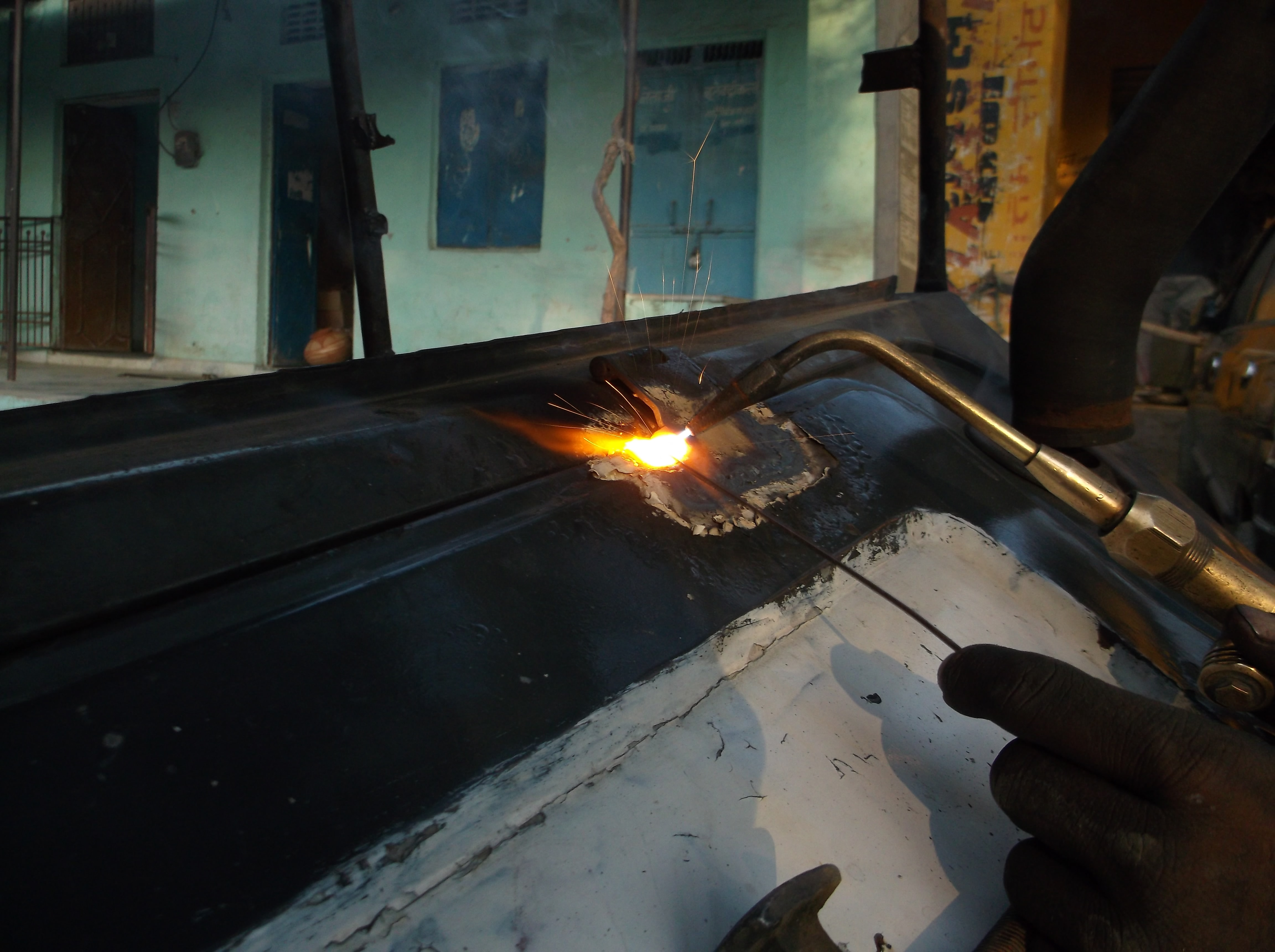 A person welding metal in a workshop