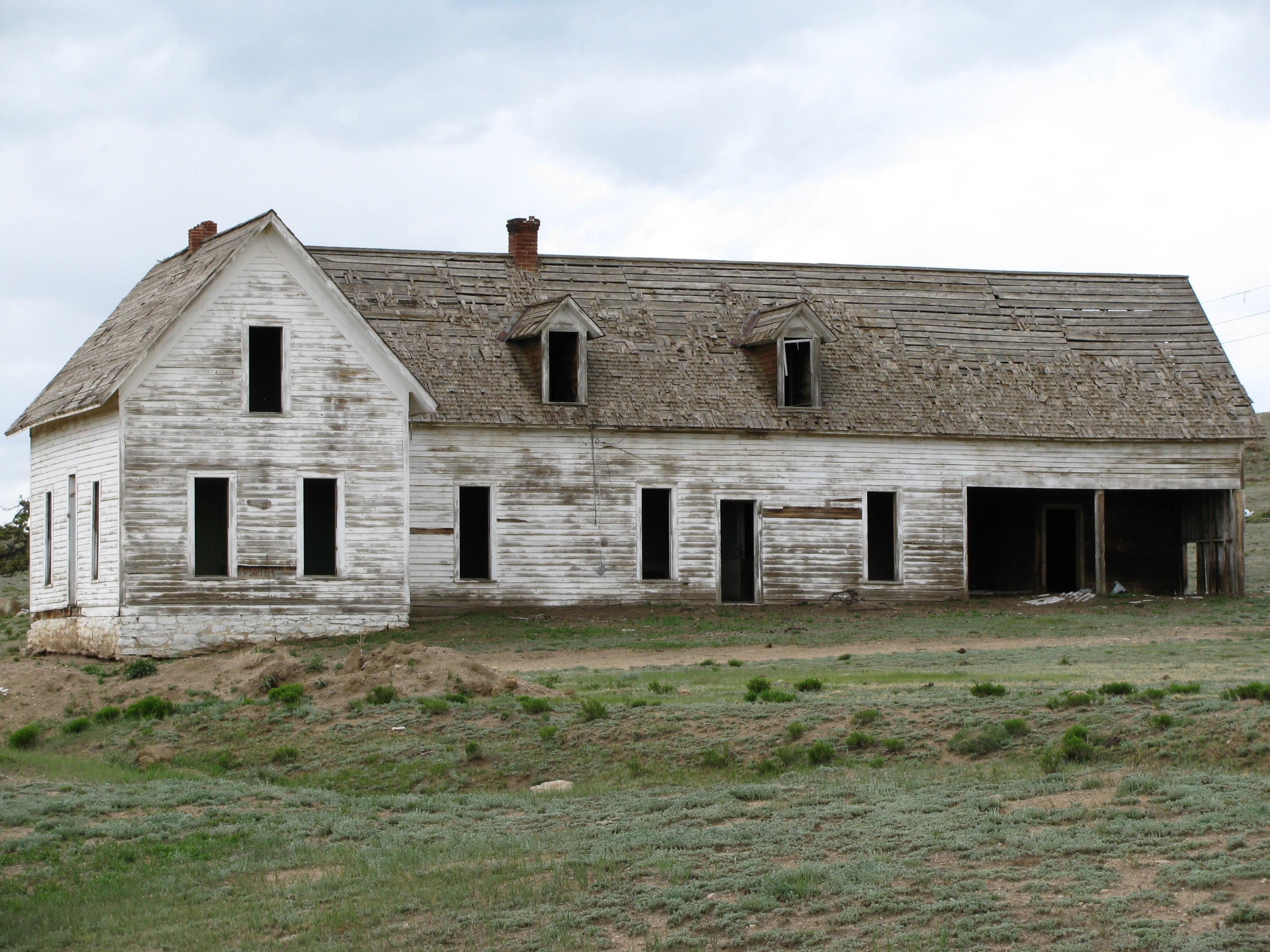 Old abandoned rural farm house with white chipped paint