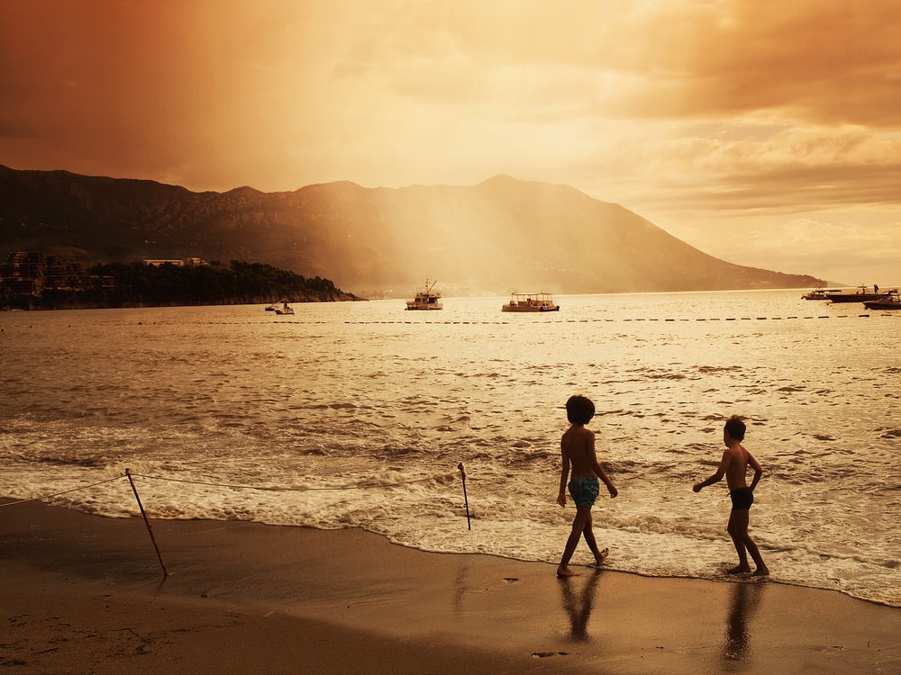 two children walking on beach during sunset