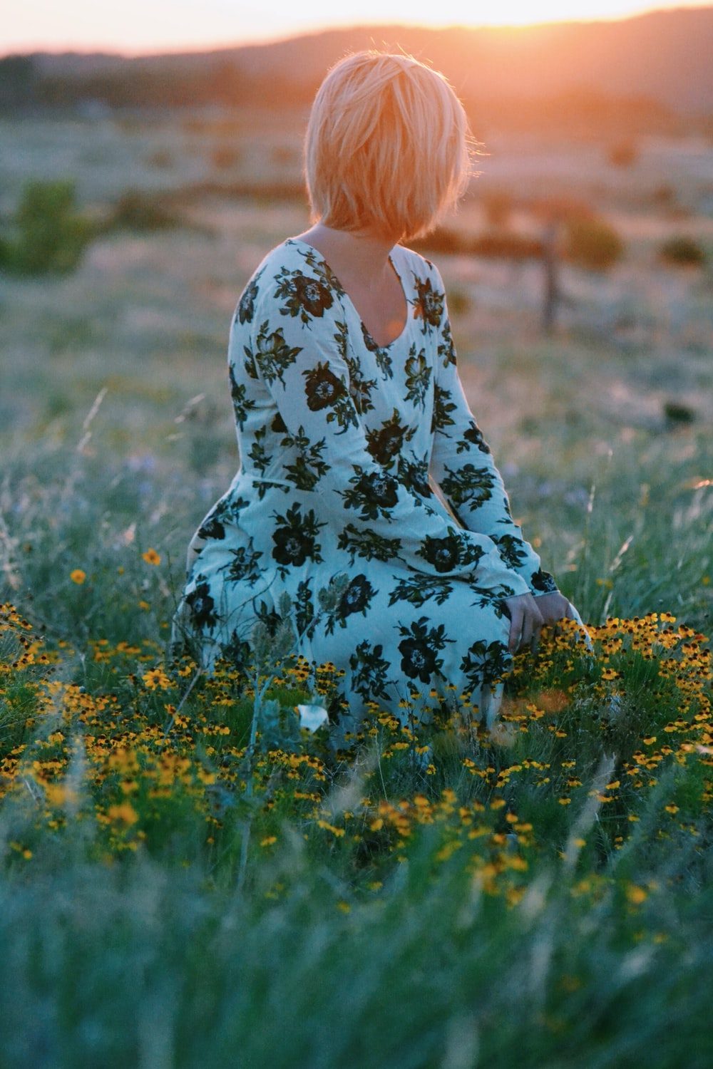 woman sitting on yellow flower field during daytime