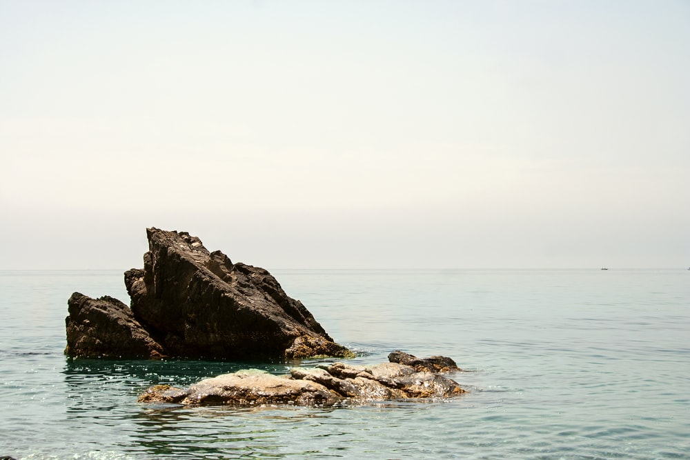 closeup photo of brown rock surrounded by body of water