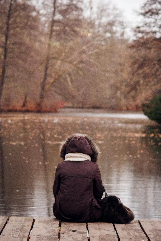 person wearing parka jacket sitting on wooden dock