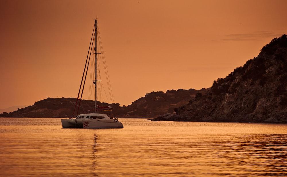 white catamaran sailing during sunset