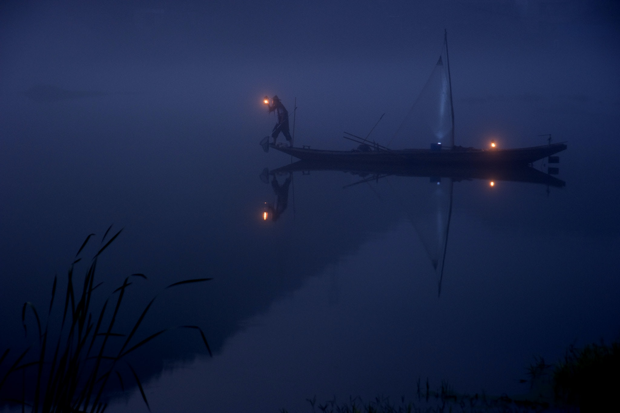 A man is trying to fish in the dark from a boat on a tranquil lake.