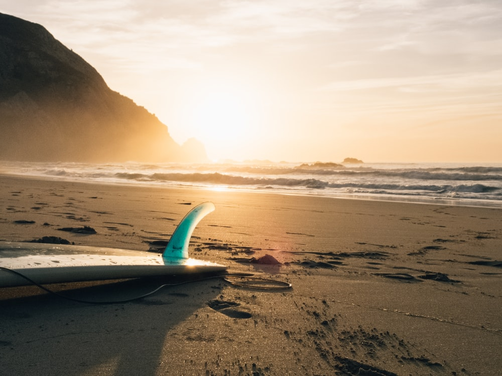 surfboard on brown sand beside ocean during sunset