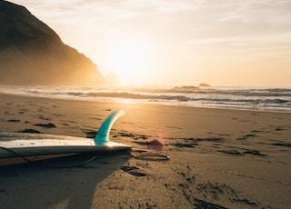surfboard on brown sand beside ocean during sunset