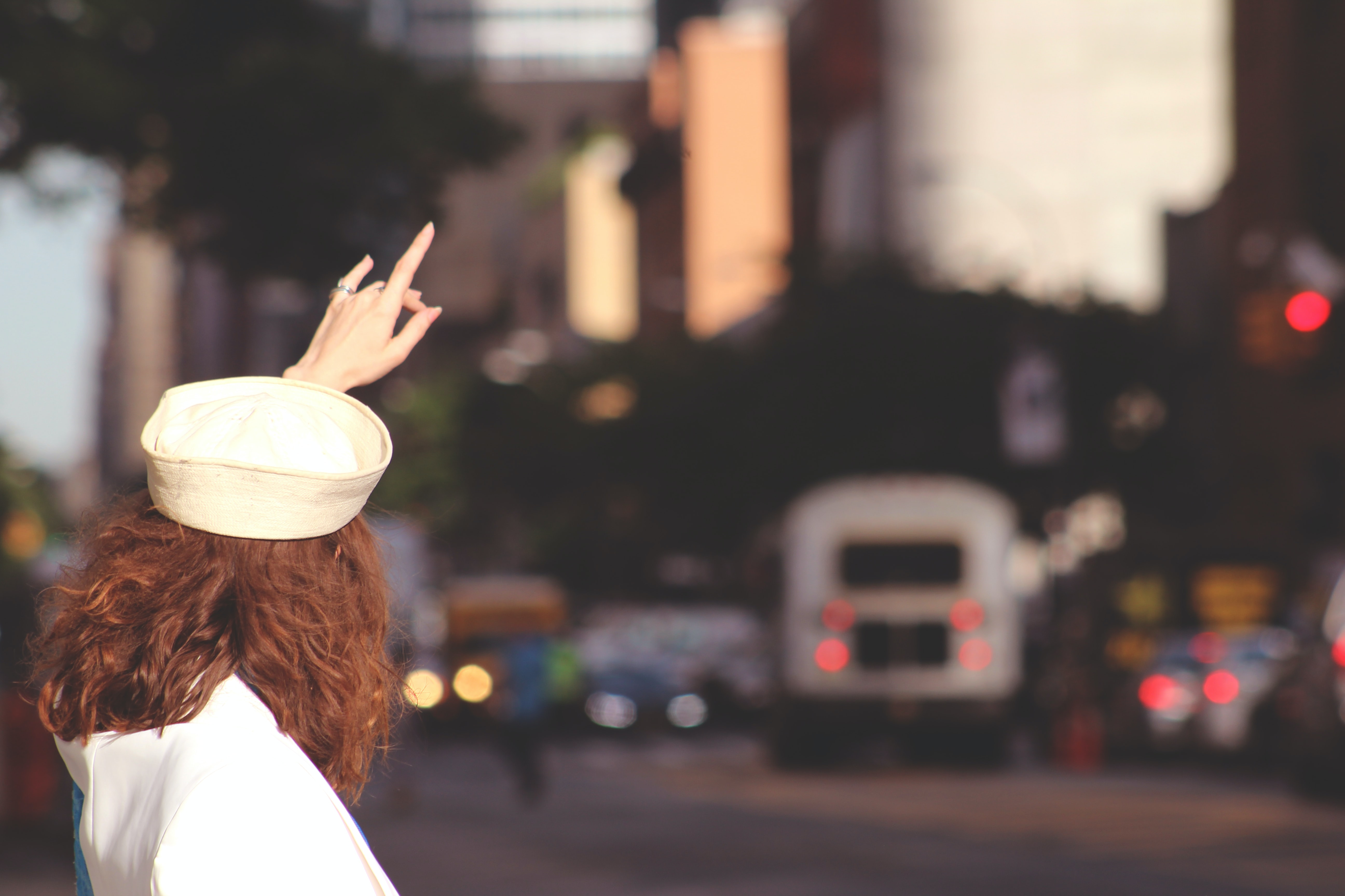 A brown-haired woman in a white hat hailing a taxi