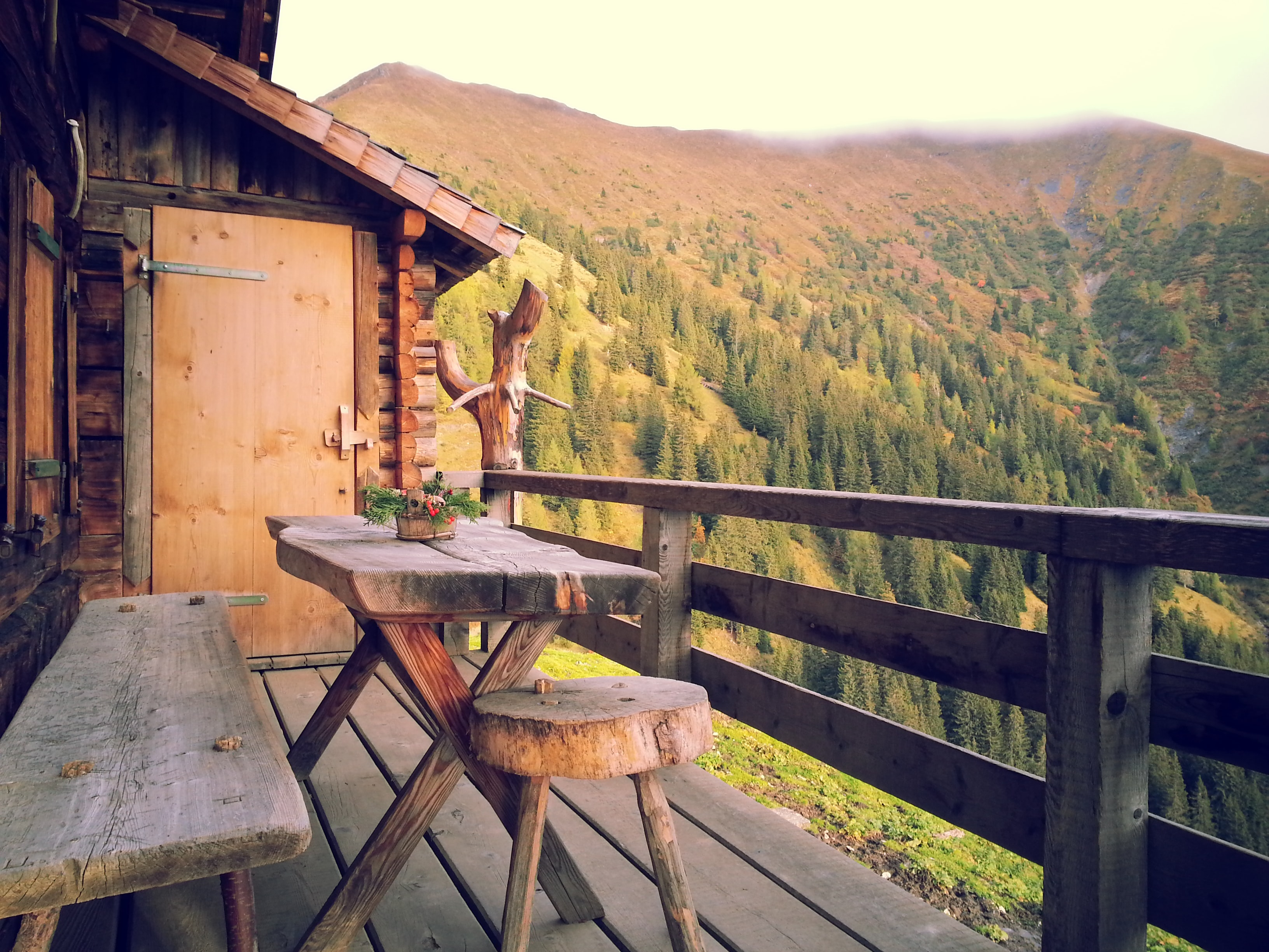 Table and chair on a cabin balcony overlooking the lush forest.