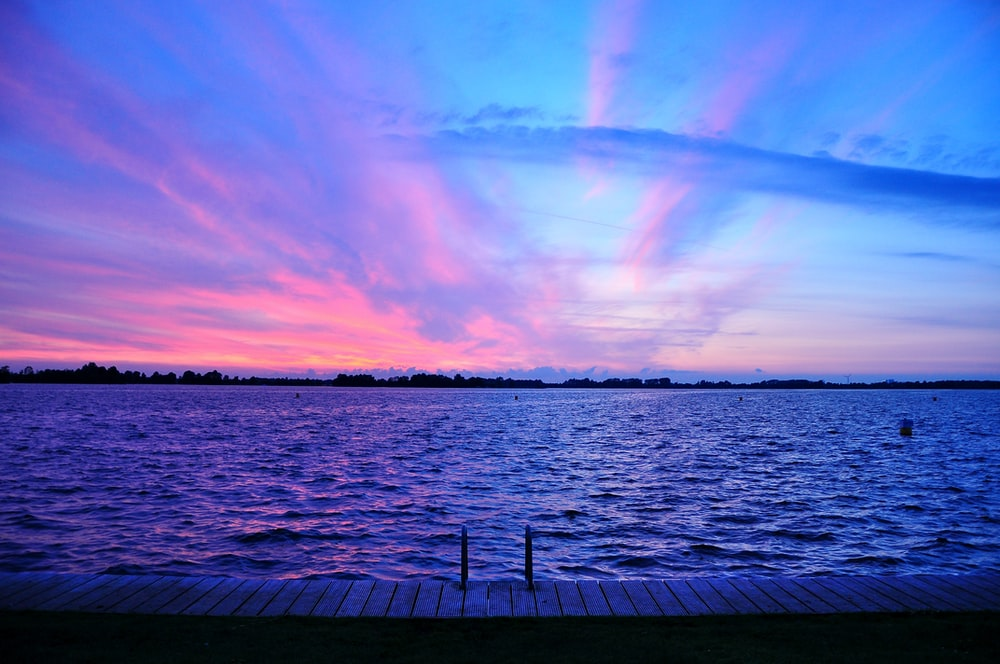 tranquil red and pink sunset over water photo by davide ragusa