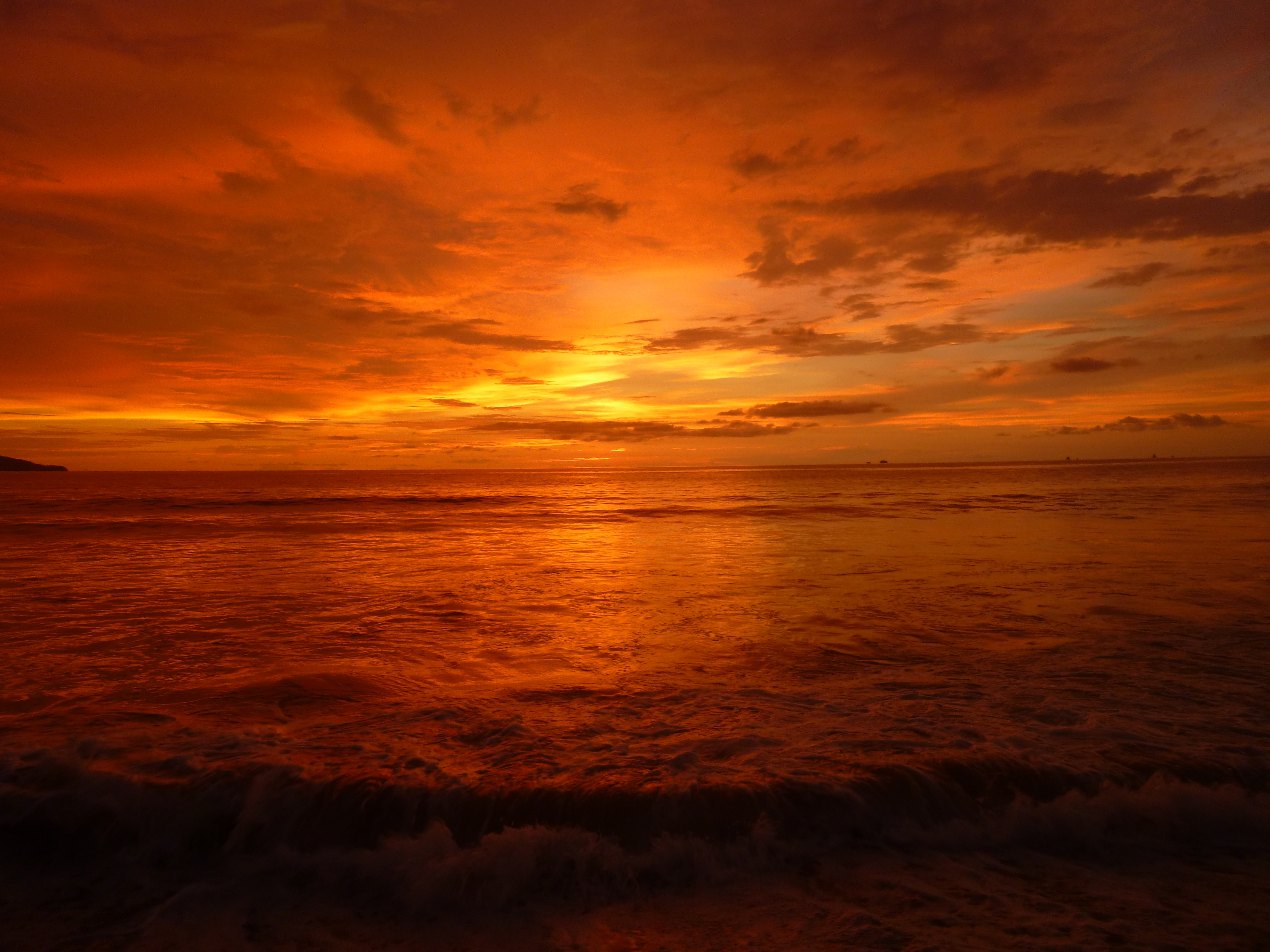 Dramatic deep orange sunset over the ocean with golden and grey wispy clouds in the sky.