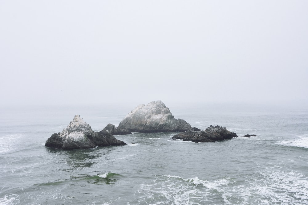 gray and black rock formation in between of body water photo