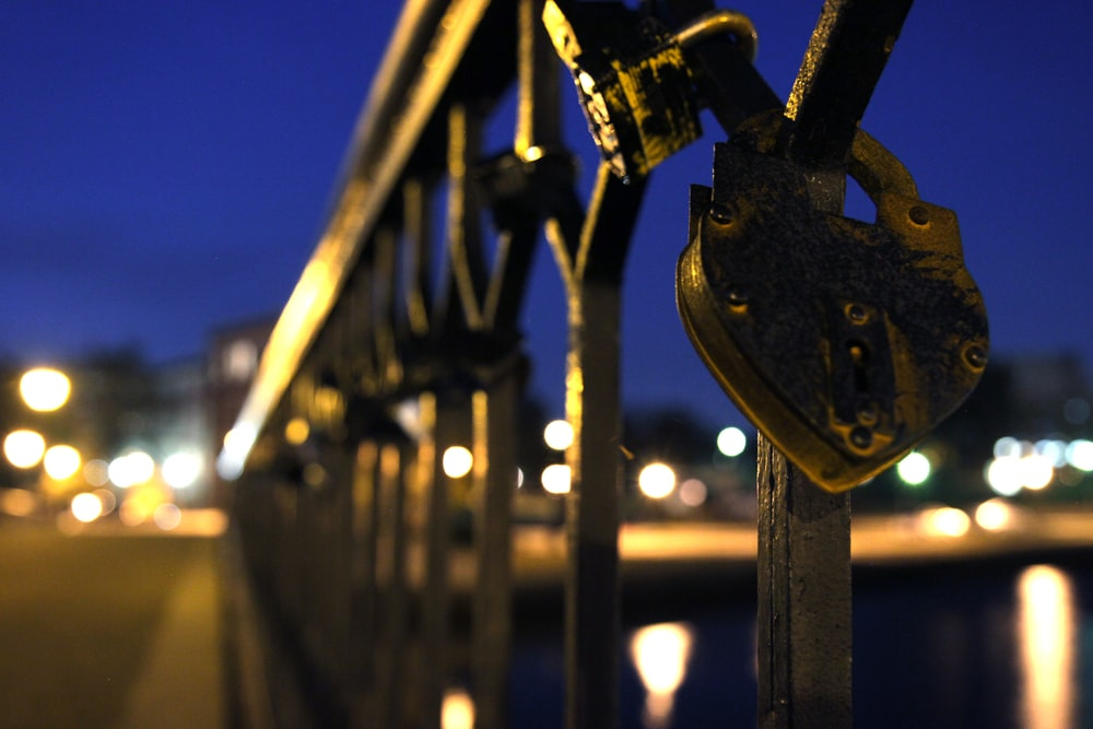 blue padlock on black metal fence during night time