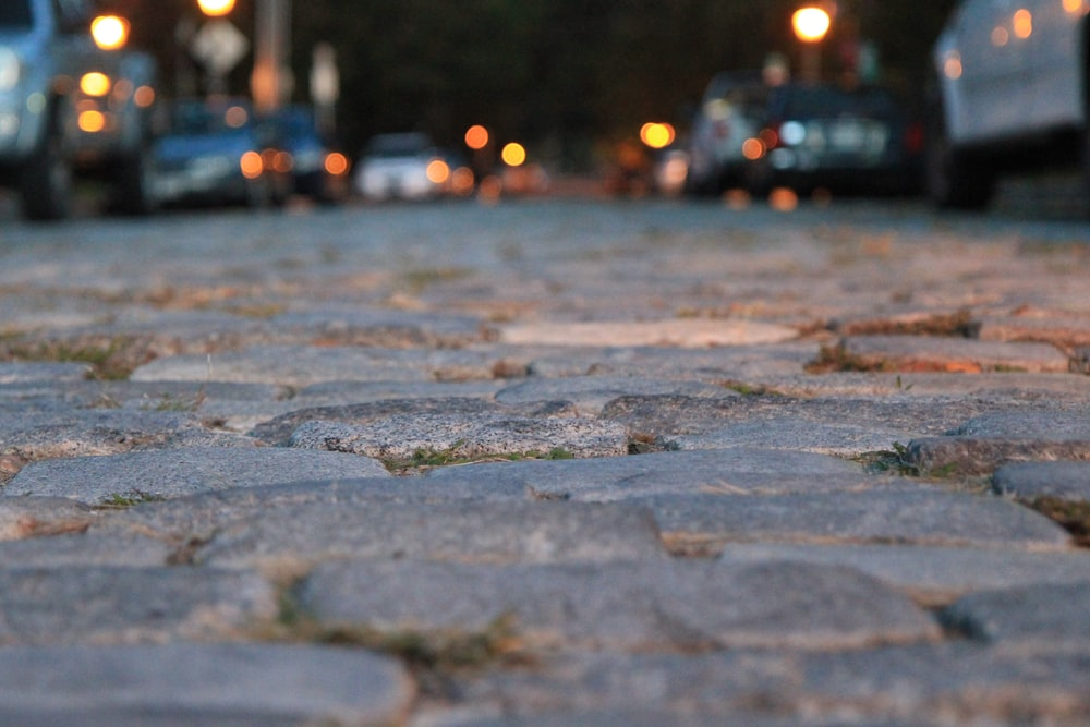 water droplets on gray concrete pavement during night time