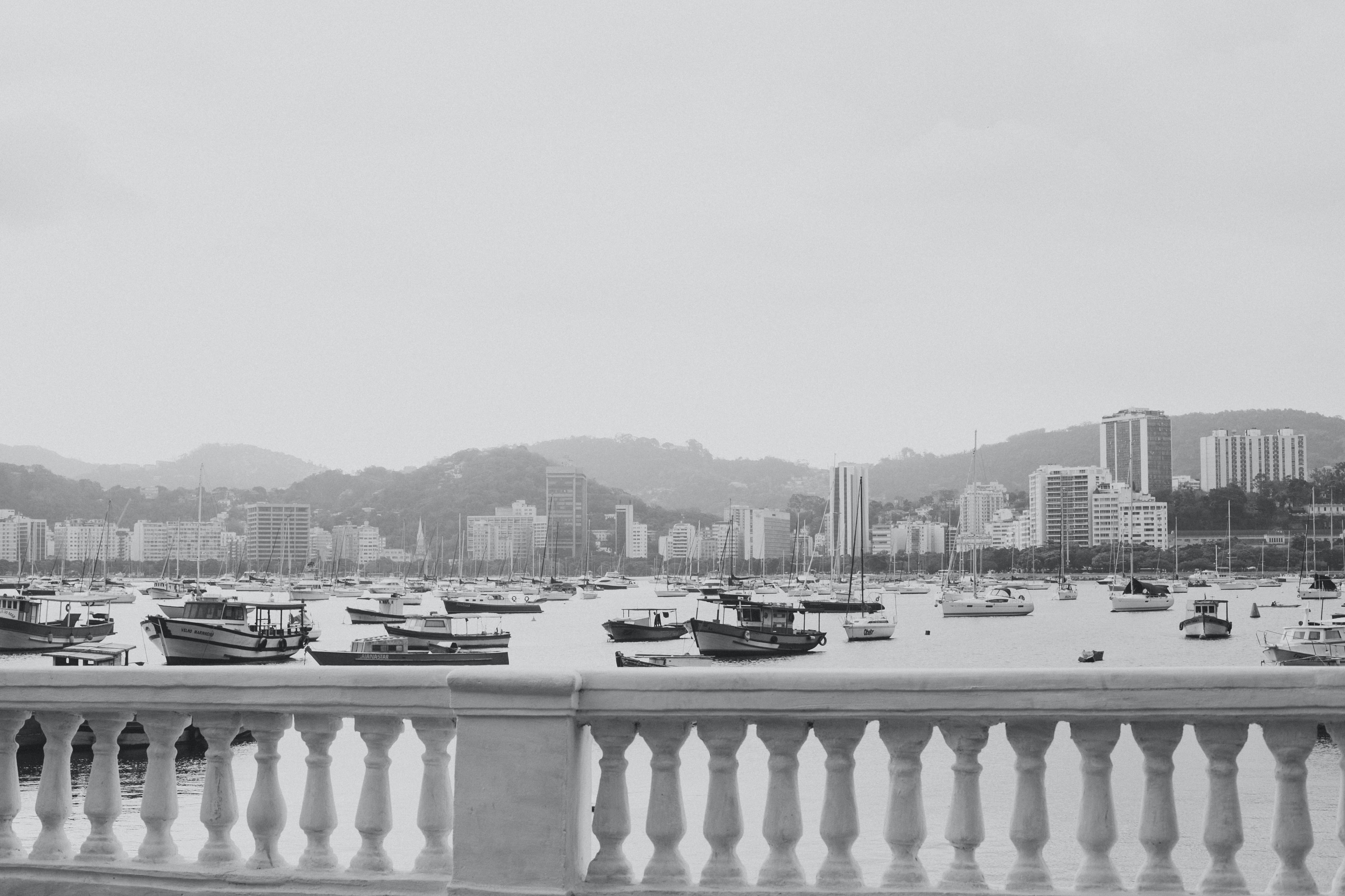 Black and white shot of marina with boats and stone wall with pillars in foreground