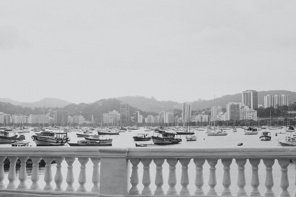 grayscale photo of boats on body of water