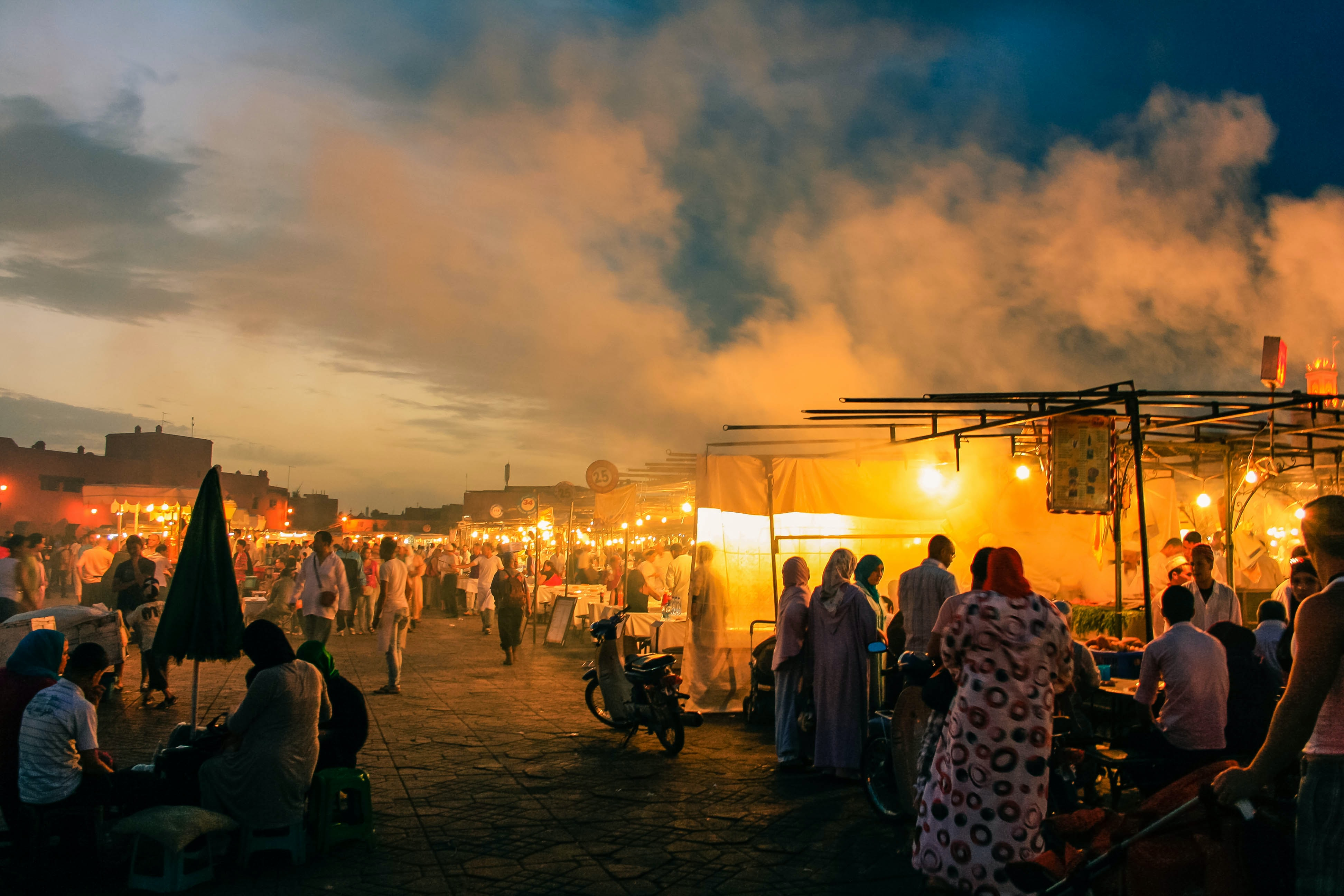 Orange glow and smoke rising up from a crowded bazaar on an evening