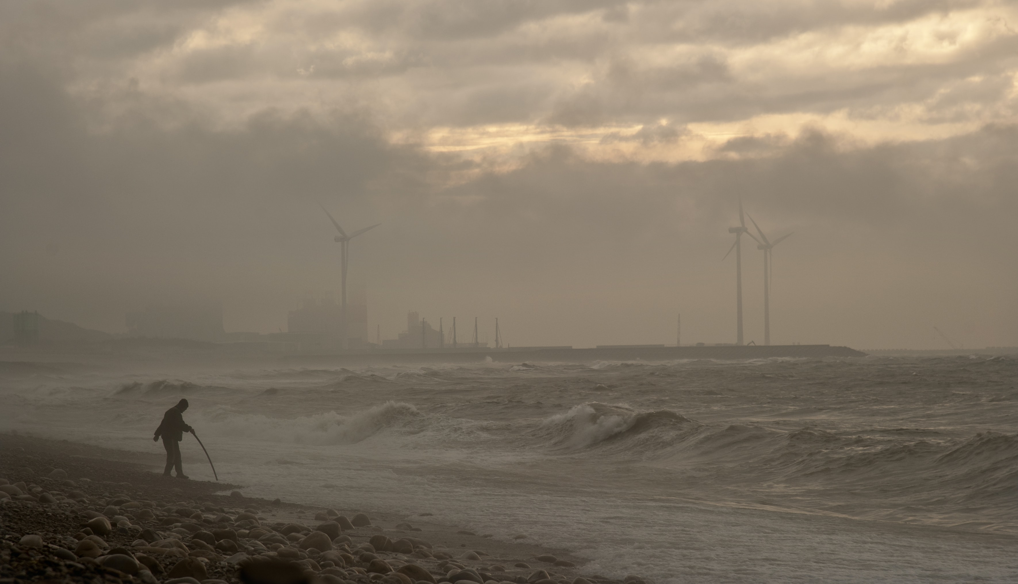 Dramatic view of the beach with rough winds and windmills in the background
