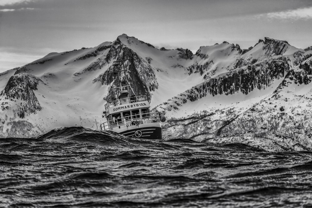 grayscale photography of ship on body of water near at snowy mountain