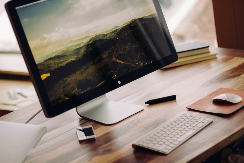 space gray iMac near Magic Keyboard on brown wooden computer desk during daytime