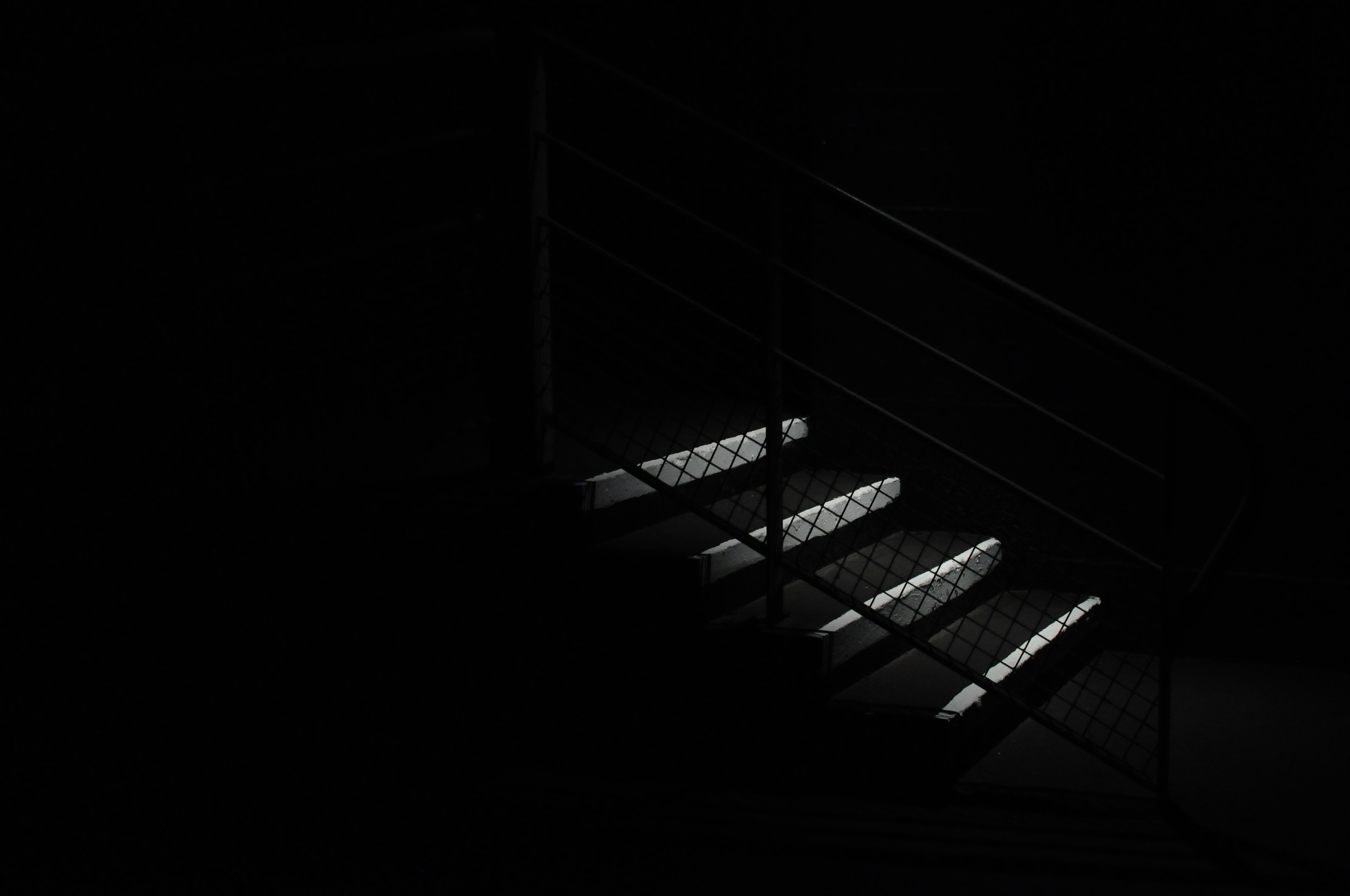 A staircase and fence style railing exposed amidst darkness