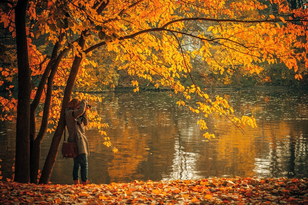 woman in brown coat standing near orange leafed tree and body of water during daytime