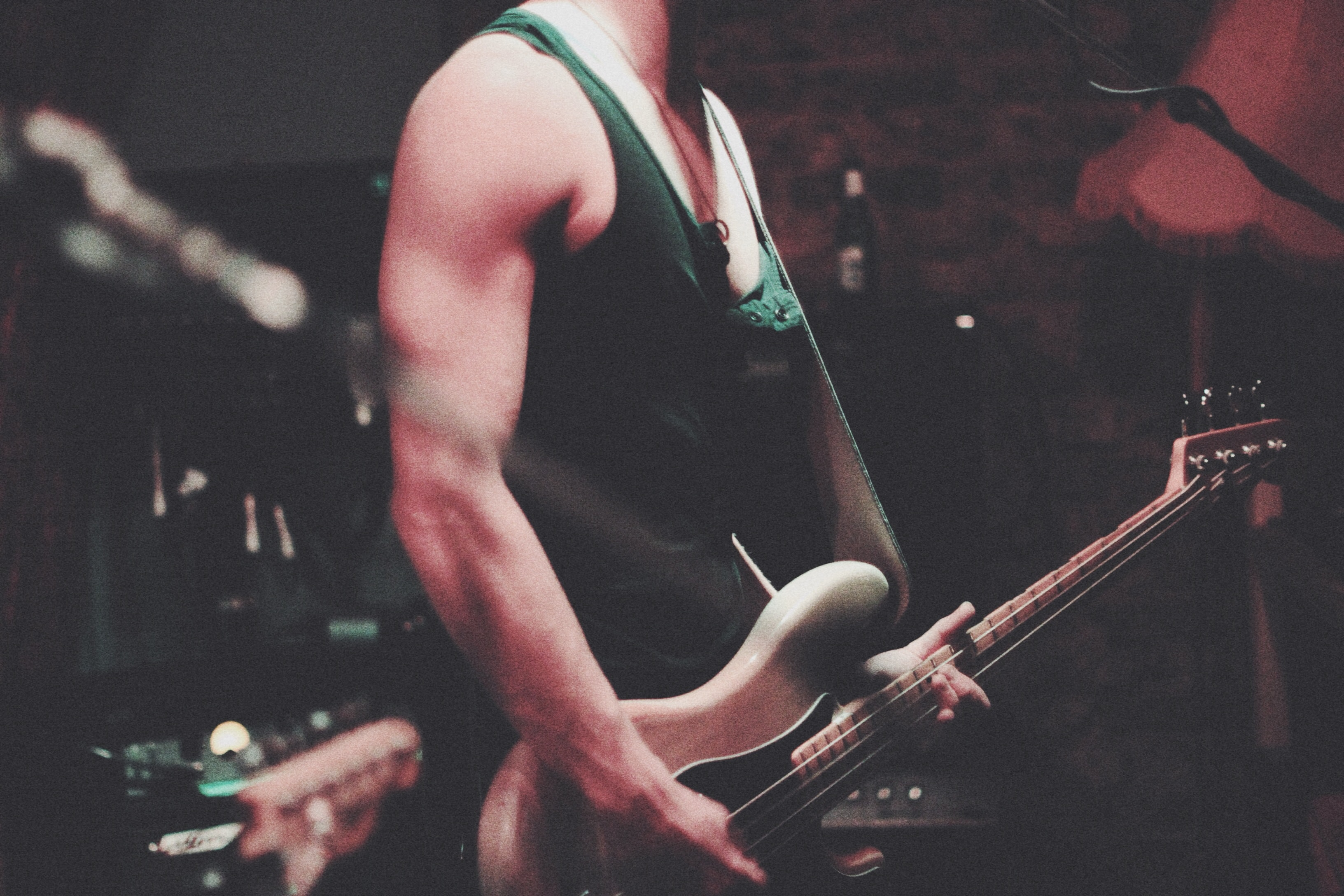 A fuzzy shot of a man with a white bass guitar