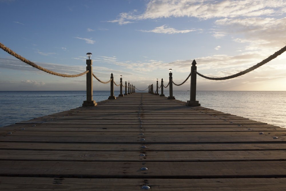 landscape photo of sea dock under stratocumulus clouds