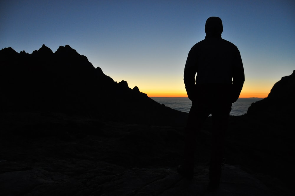 silhouette of person on top of mountain under blue sky during orange sunset