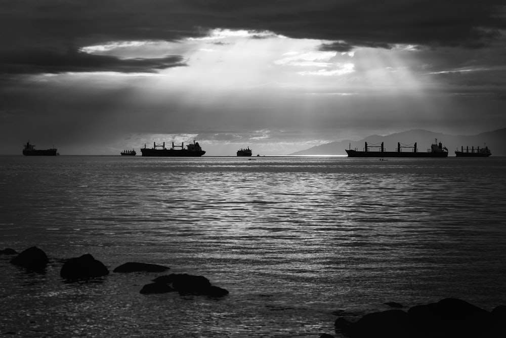 grayscale photo of ships on water
