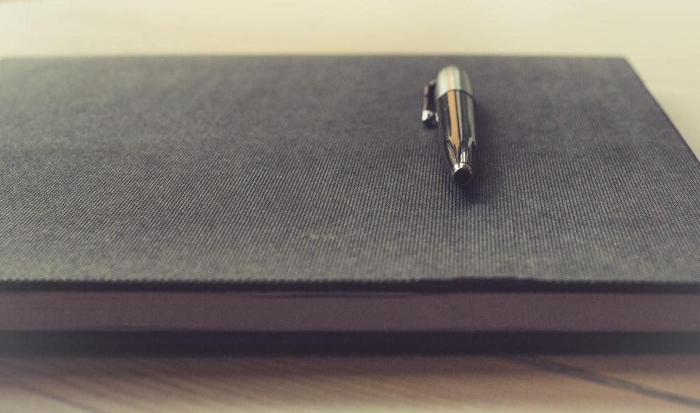 gray click pen on black book