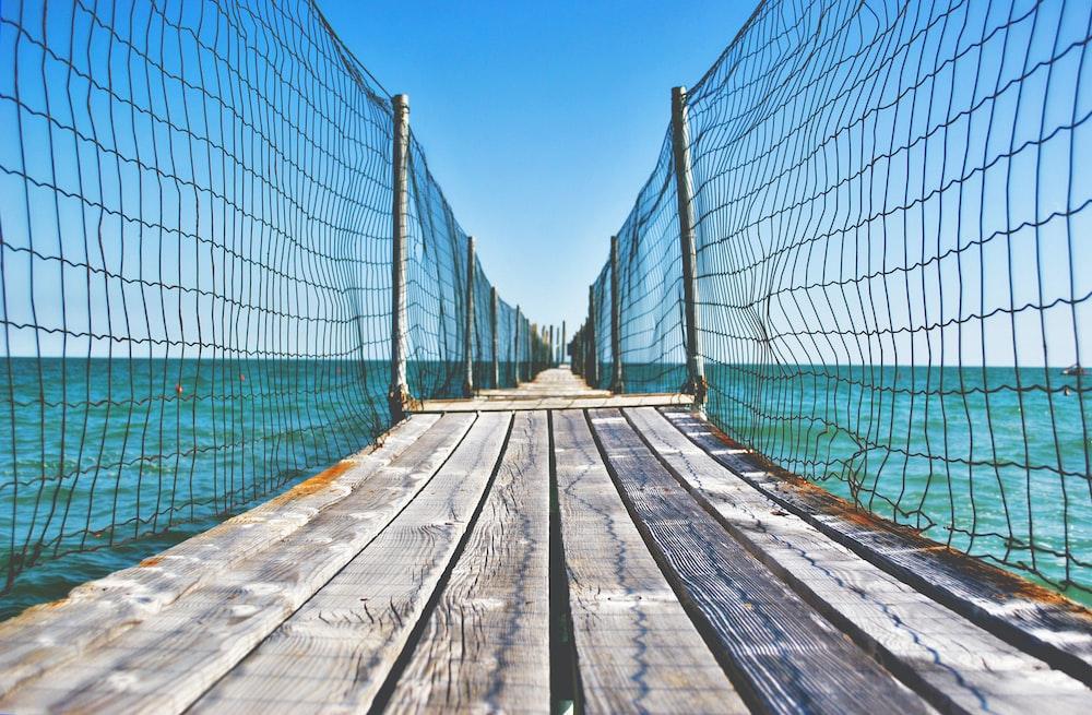 brown wooden bridge with net over body of water