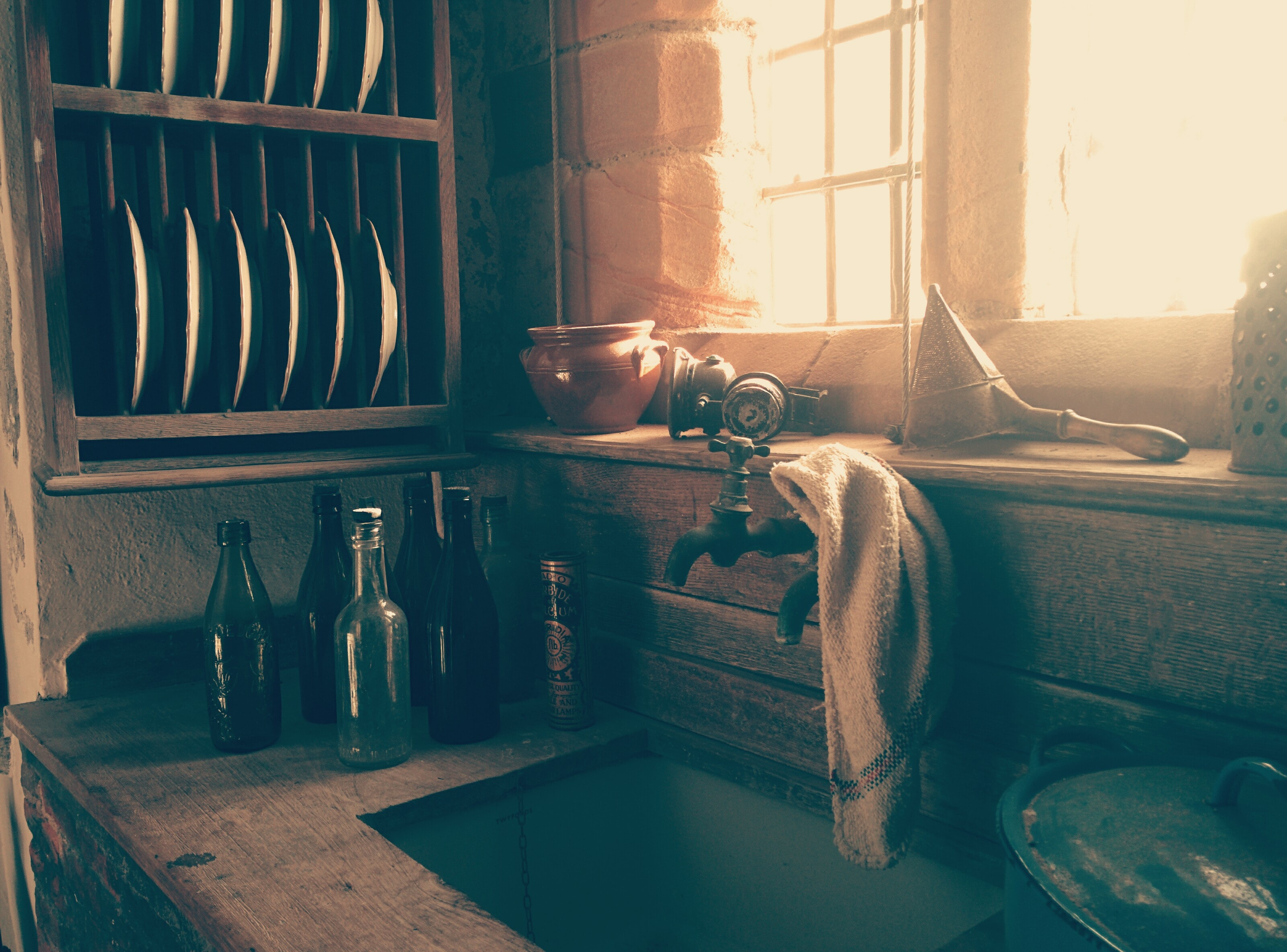 A rustic sink with bottles next to it, plates on a shelf, and a rag on the faucet