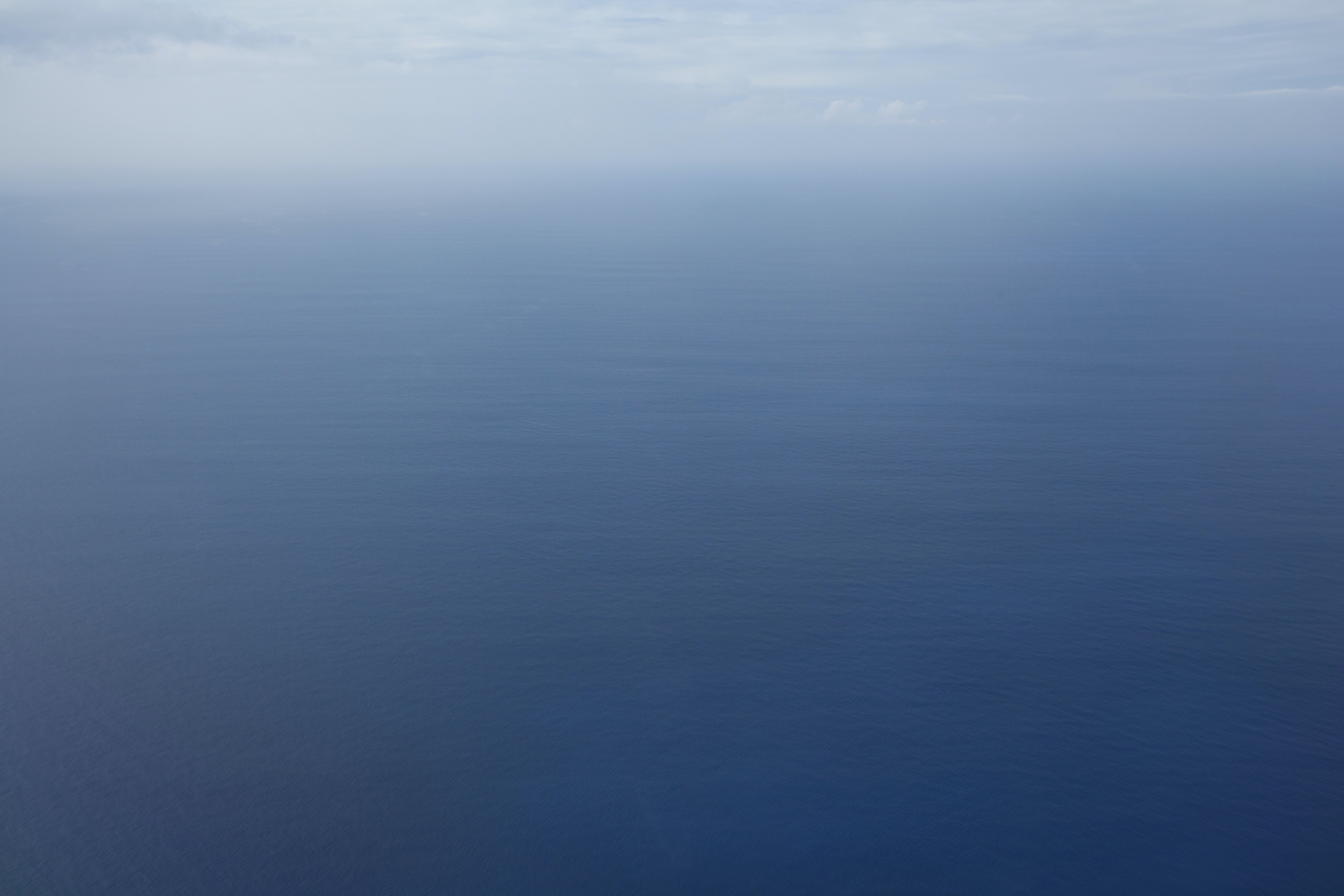 Still ocean waters disappear into the blue horizon covered in clouds