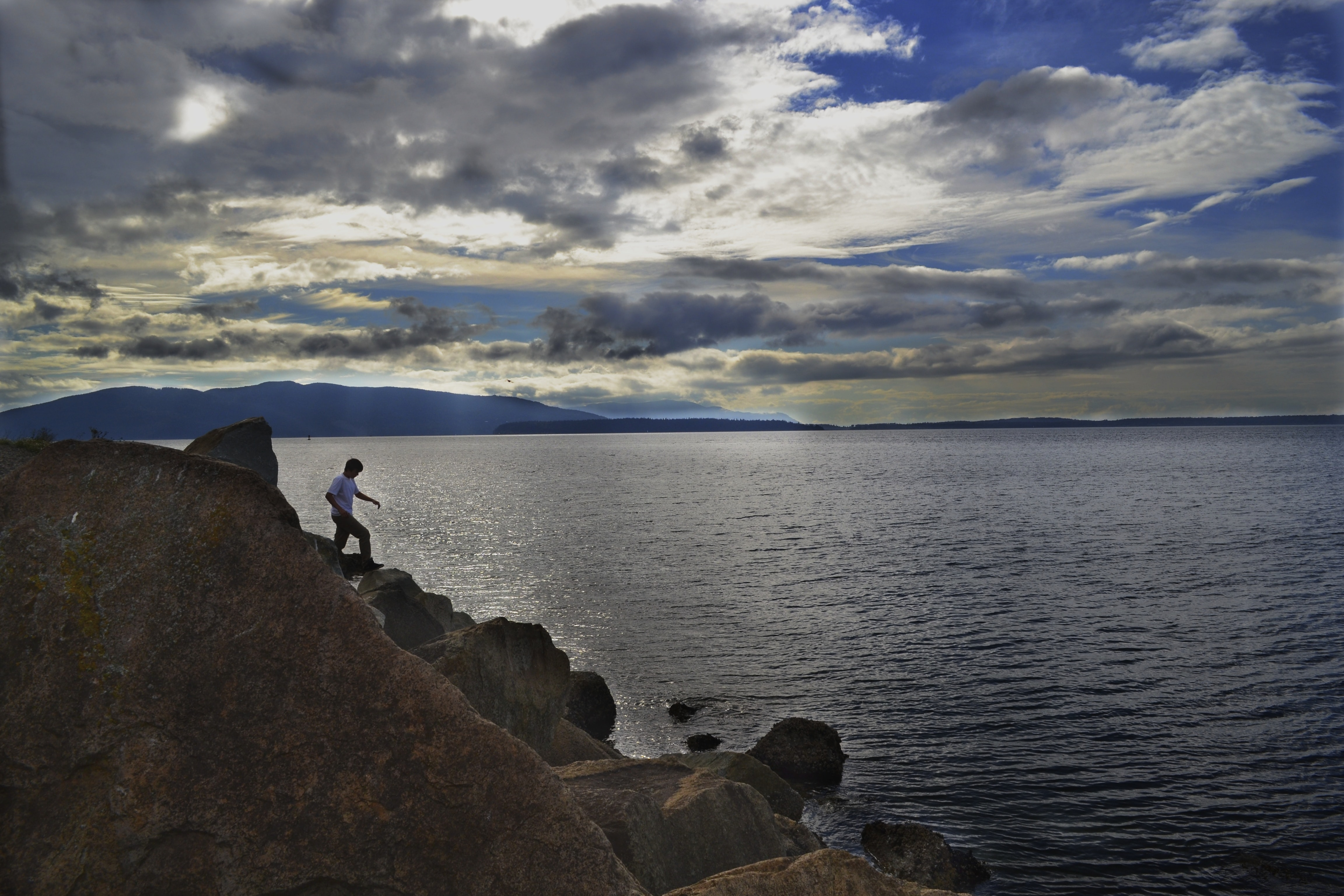 A man climbing down large rocks on the shore of a lake