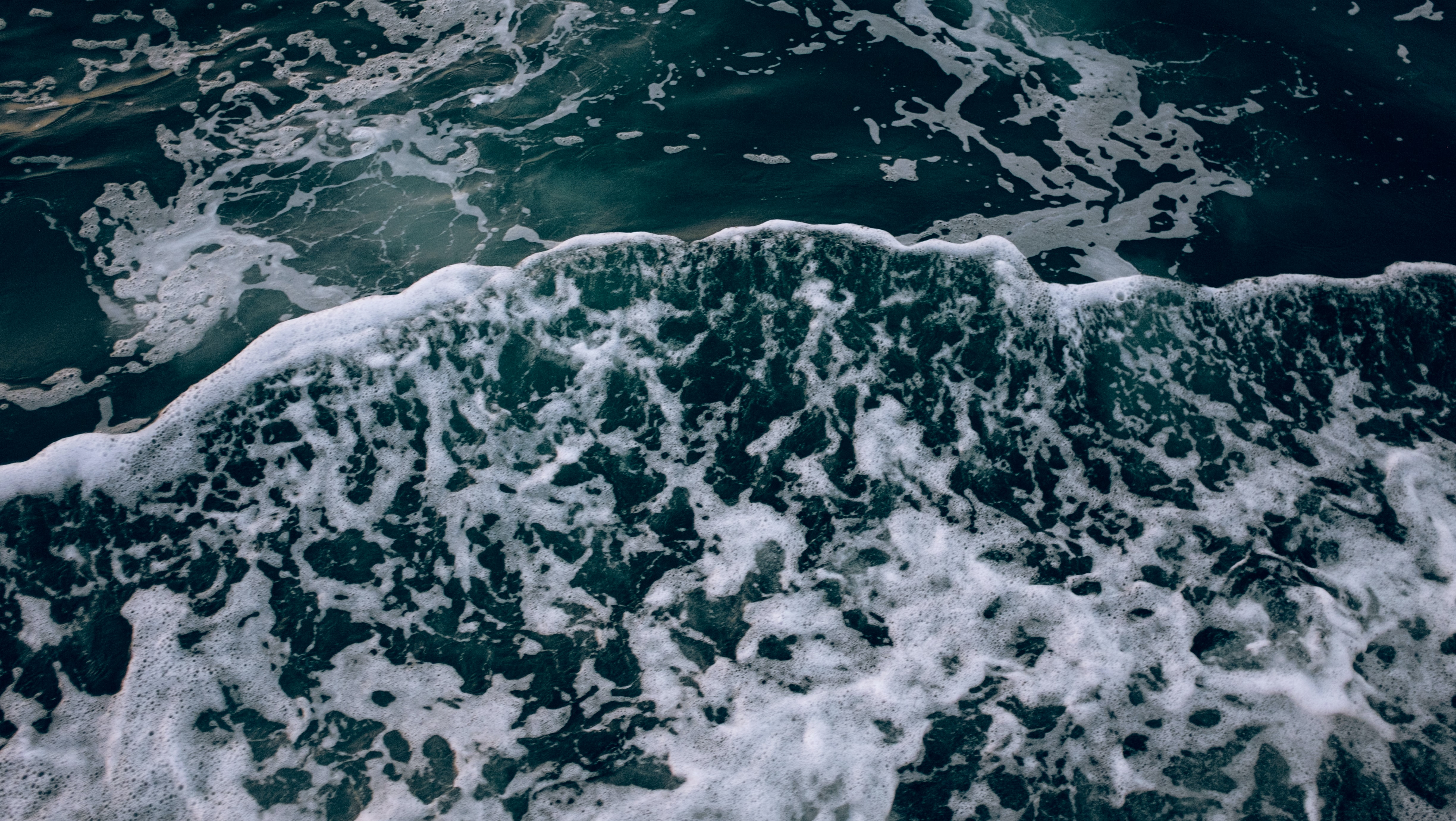 The frothy foamy deep blue waves of the ocean