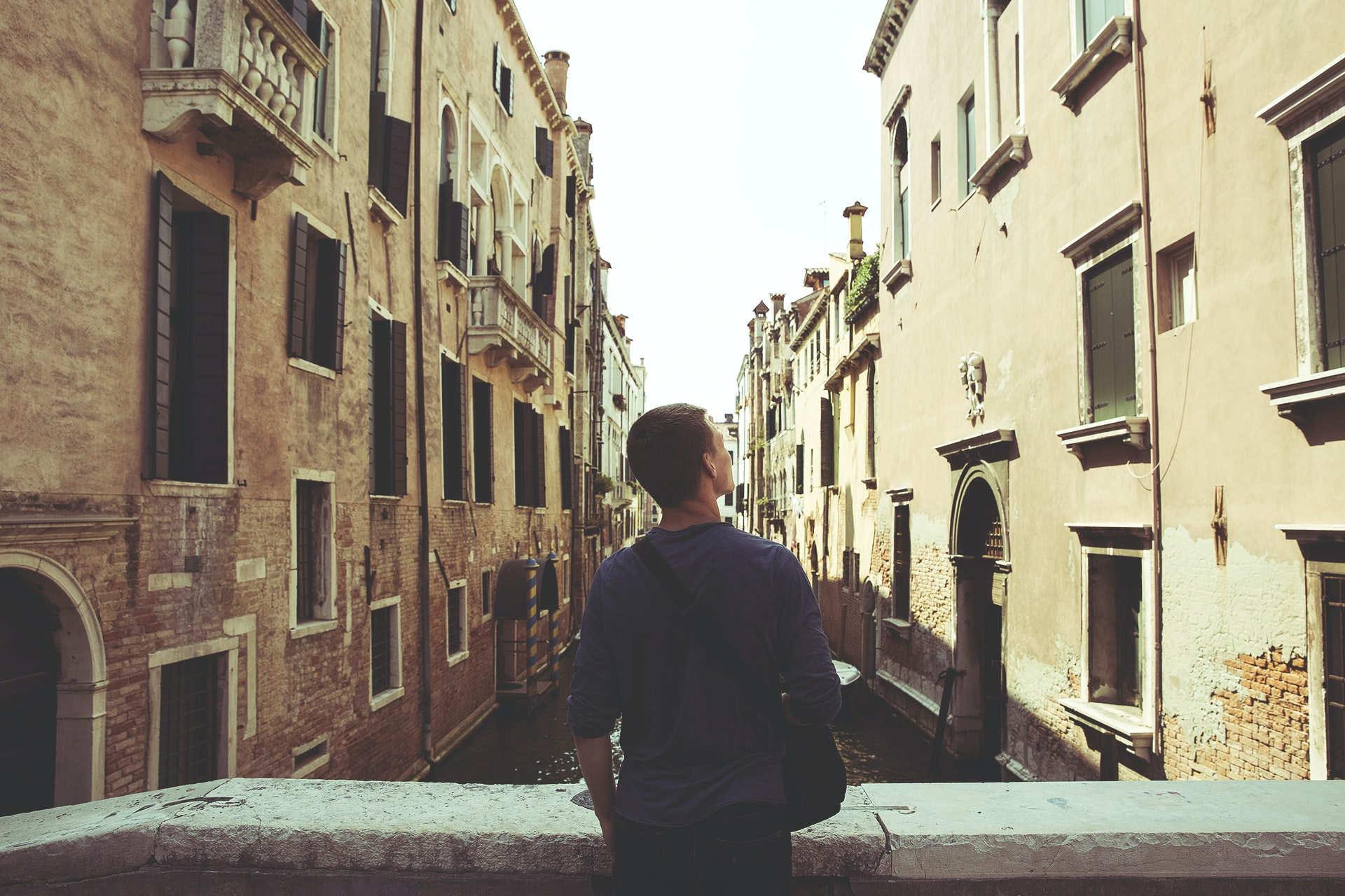 A man admiring old buildings over a canal in Venice