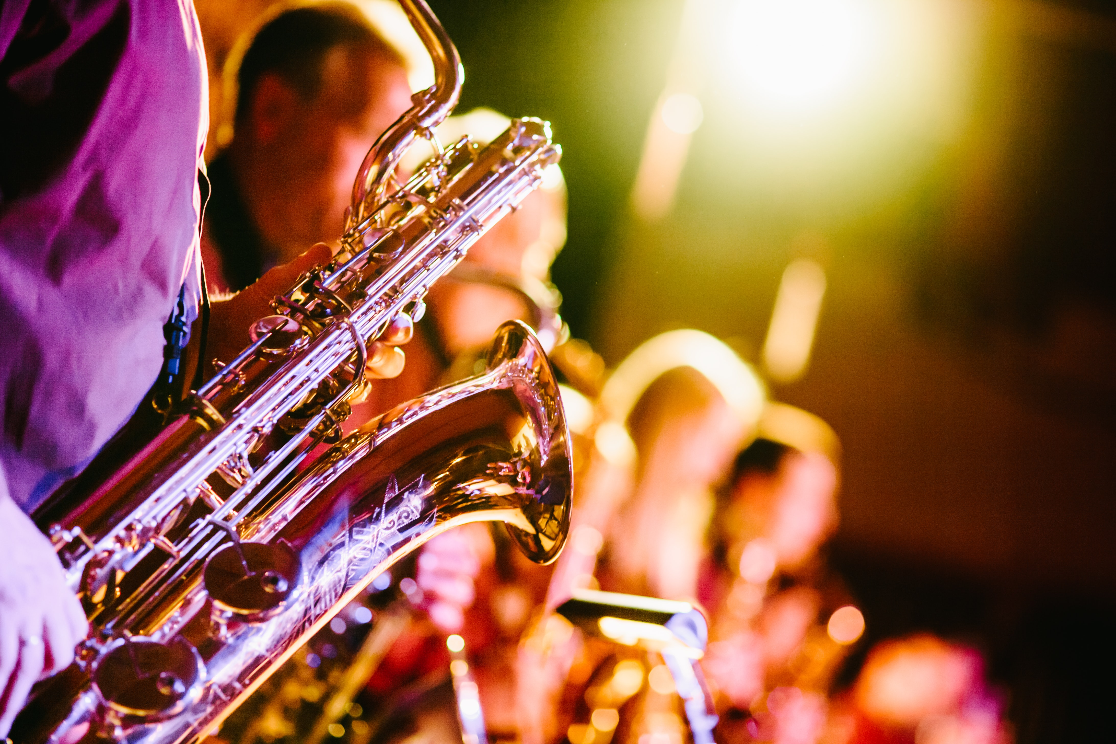 A close-up of a saxophone held by one of the band members during a jazz concert