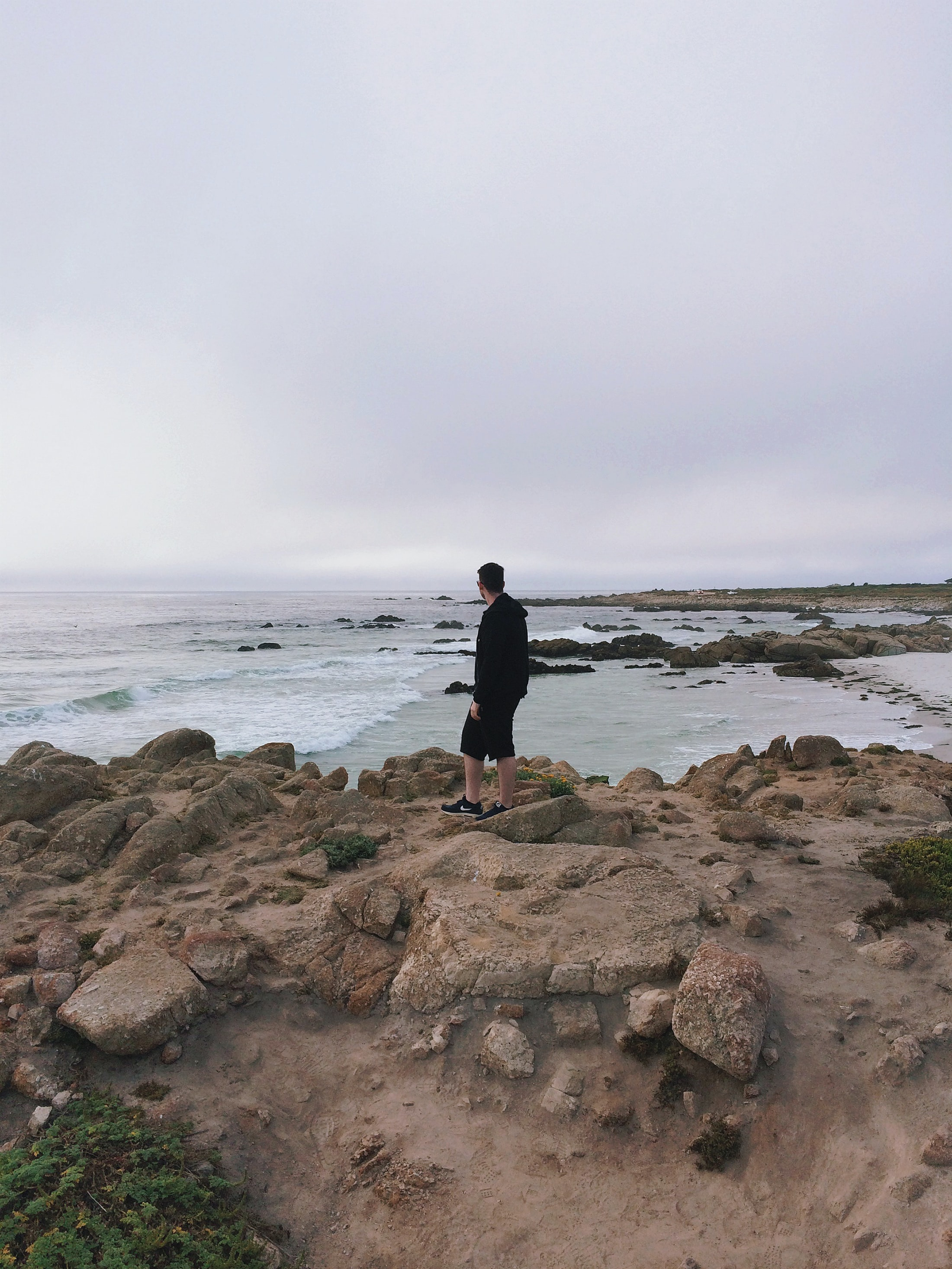 A man standing on a rocky shore on a cloudy day