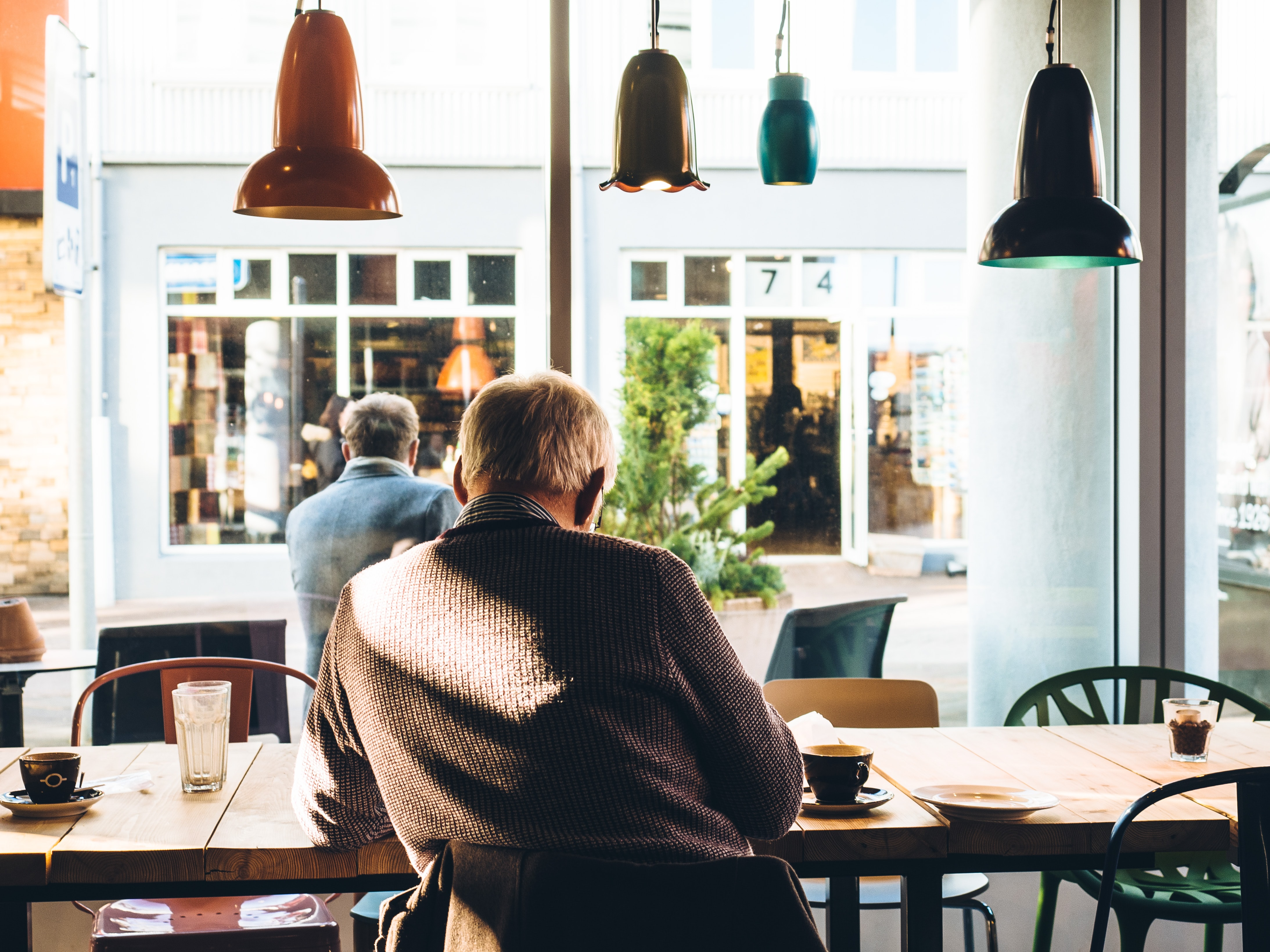man in chair with table beside coffee