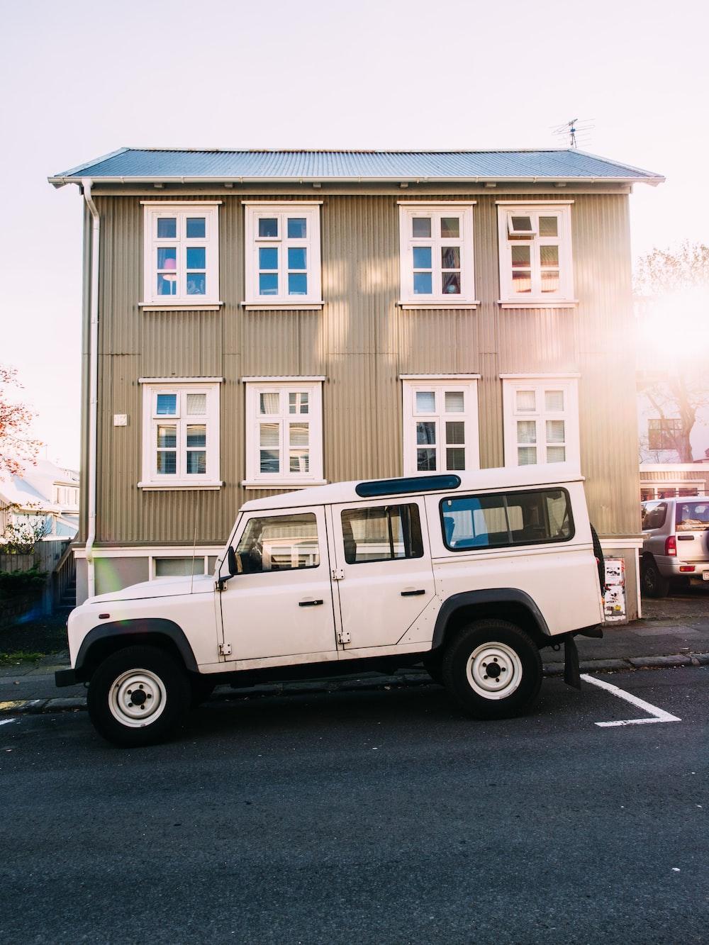 white vehicle near beige house
